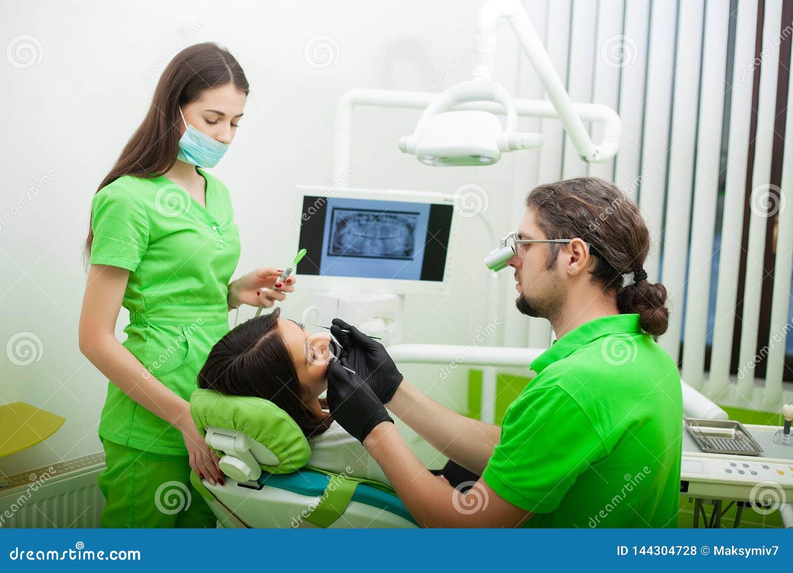 De tandartsman behandelt tanden aan cliënt in tandbureau