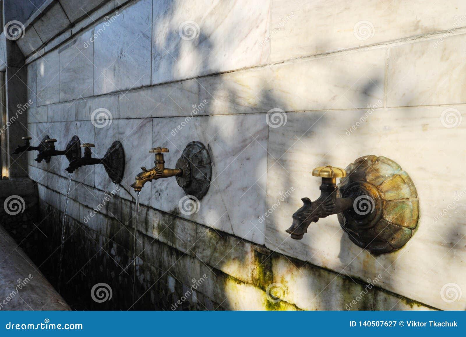 De tapkranen van het bronswater in de stad met water voor het drinken