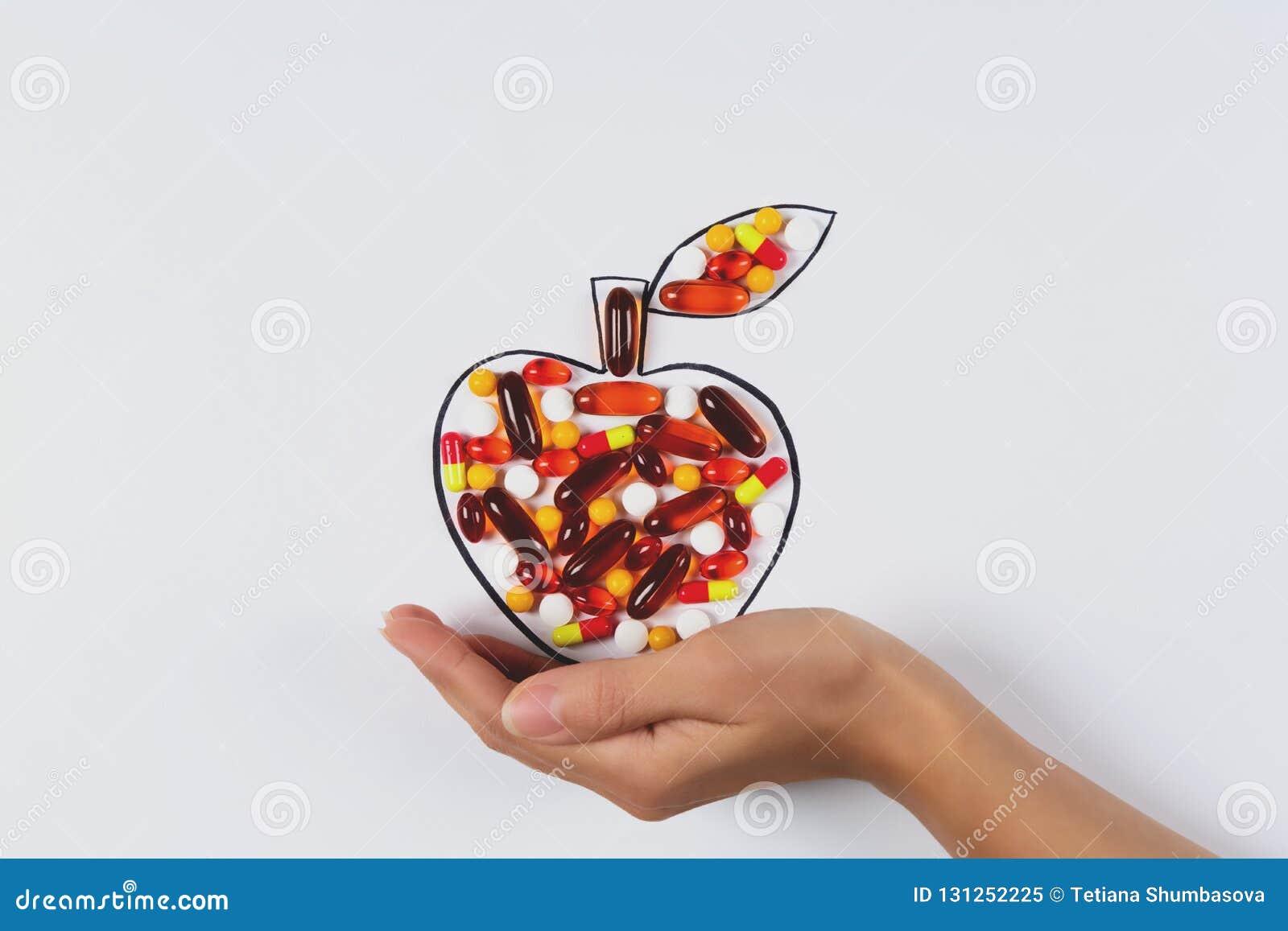De tekeningsappel van de handholding met kleurrijke capsules en pillen op witte achtergrond Gezondheidszorgvitaminen of synthetis