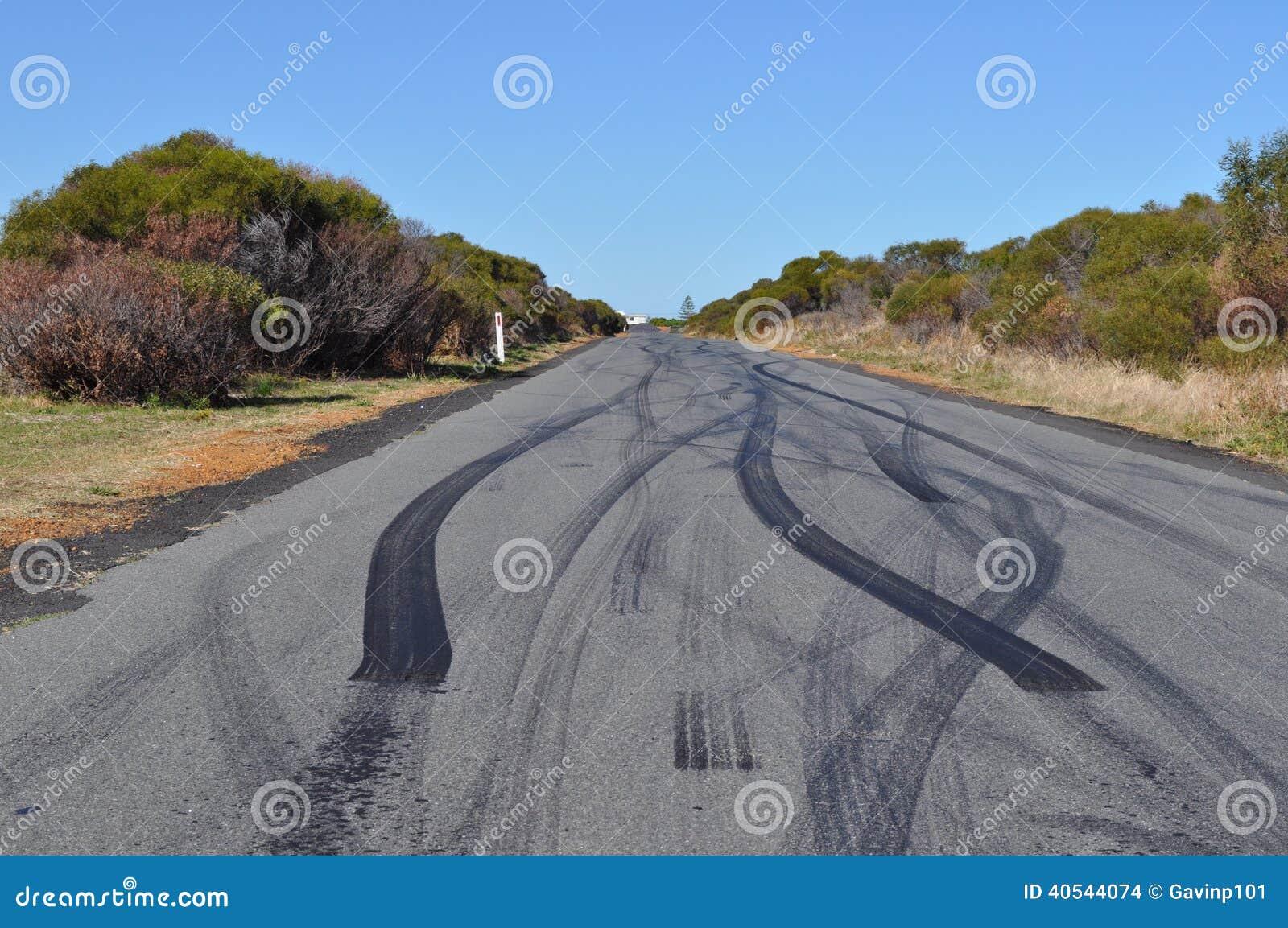 De tekens van de de bandsteunbalk van de autoband op stedelijke asfaltweg