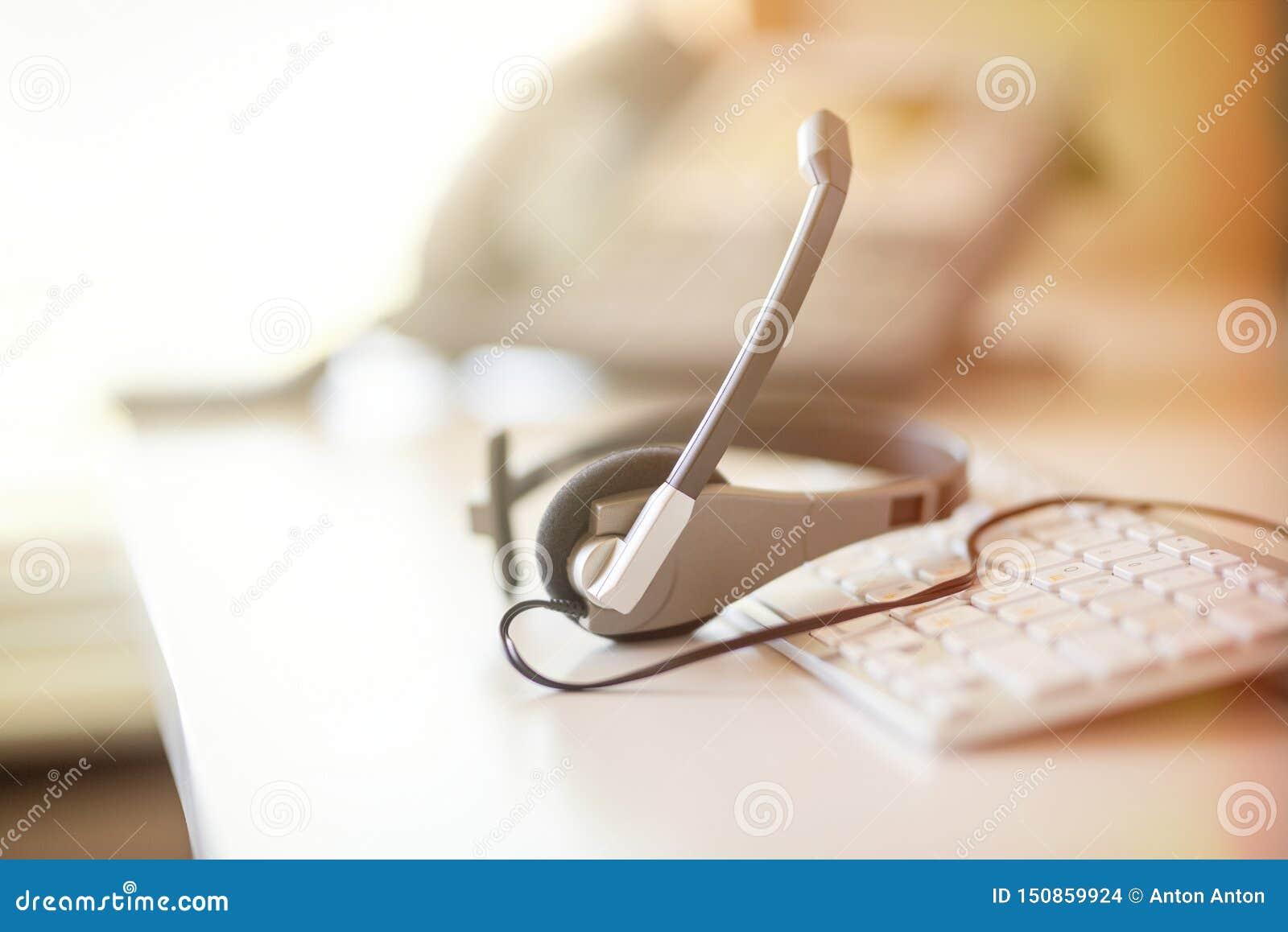 De telefoon en het toetsenbord van de hoofdtelefoonhoofdtelefoon spreken, steunen, mededeling, call centre en klantenservice, bed