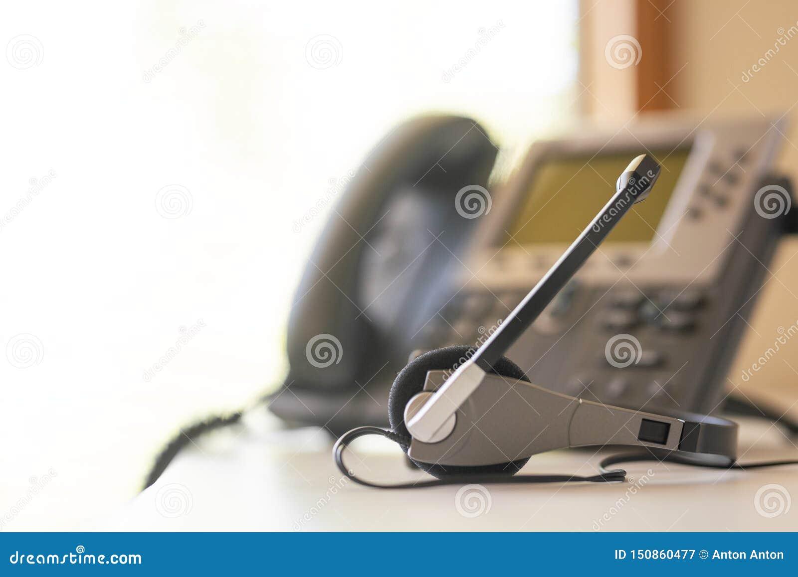 De telefoon en het toetsenbord van de hoofdtelefoonhoofdtelefoon spreken, steunen, mededeling, call centre en klantenservice