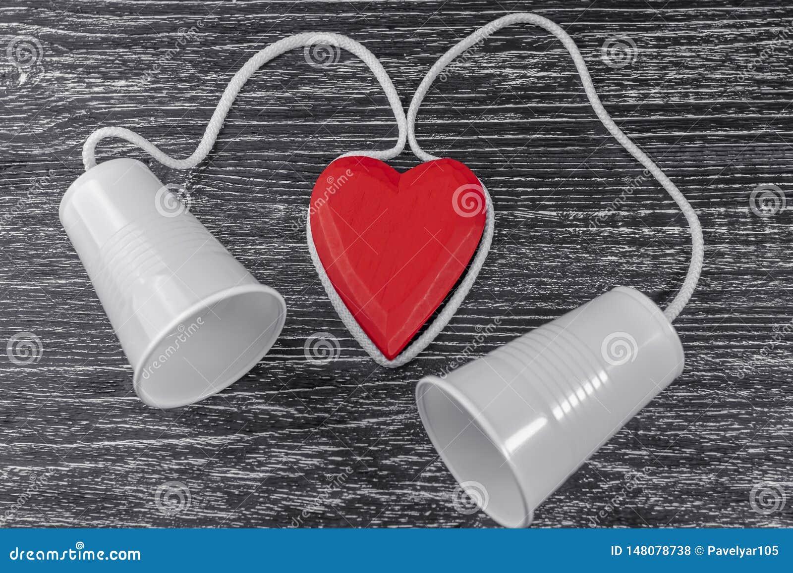 De telefoon wordt gemaakt van witte plastic koppen en een witte kabel gelegd rond een rood houten hart