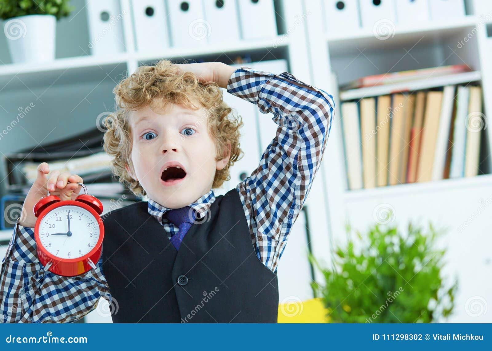 De teleurgestelde jong geitjewerkgever die een grote rode wekker in zijn hand houden die u is laat voor het werk voorstellen