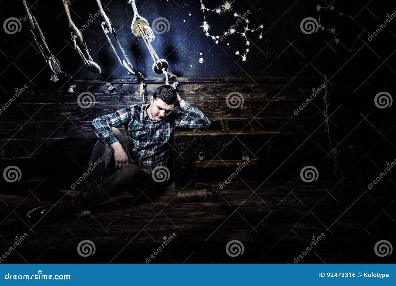 De teleurgestelde kerel zit dichtbij een borst, houdend glasfles en probeert