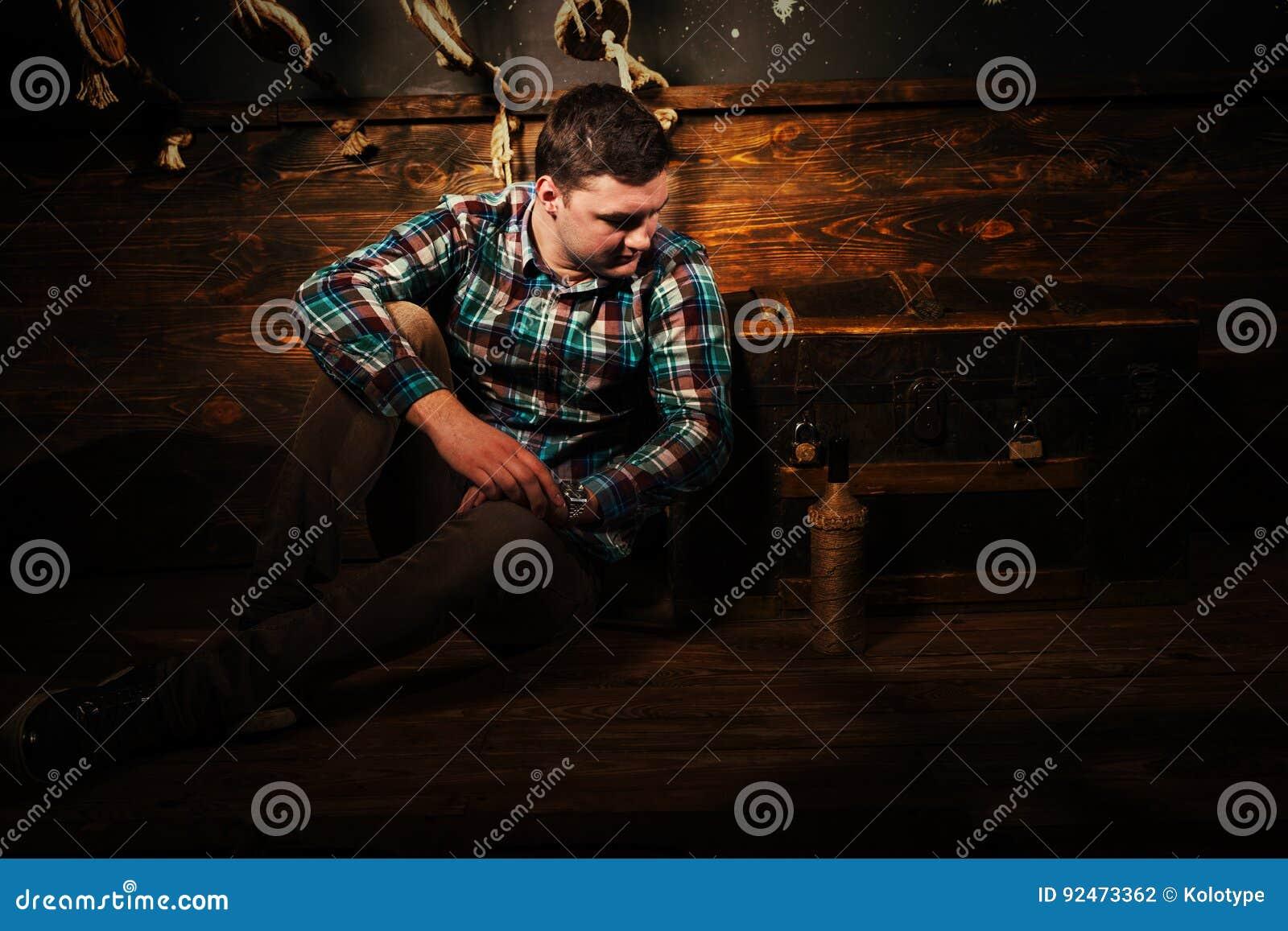 De teleurgestelde mens zit dichtbij een borst, houdend glasfles en probeert