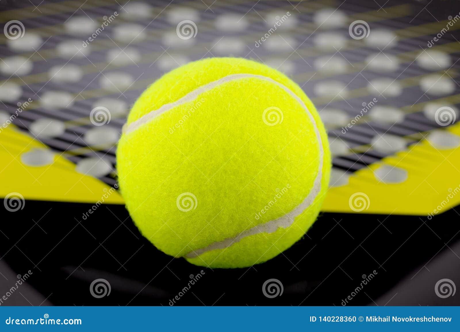 De tennisbal ligt op een racket voor het spelen van strandtennis