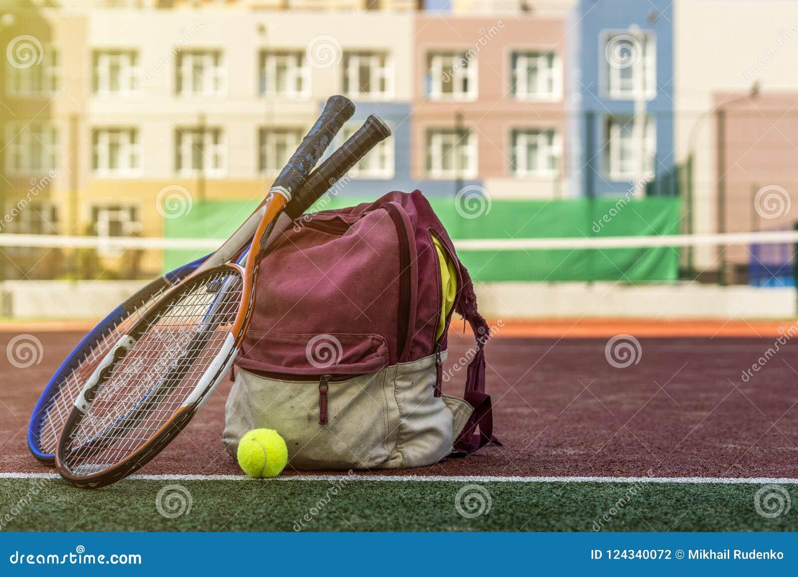 De tennisrackets met een bal dichtbij de sport doen met materiaal op het hof op de zomerdag in zakken