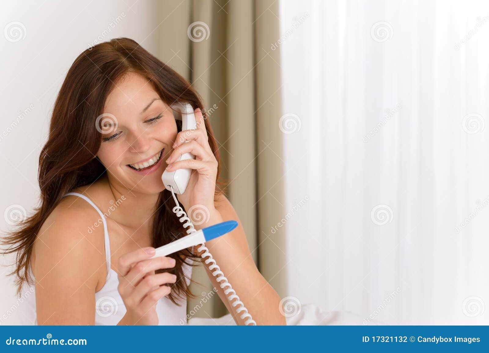De test van de zwangerschap - gelukkige vrouw op telefoon