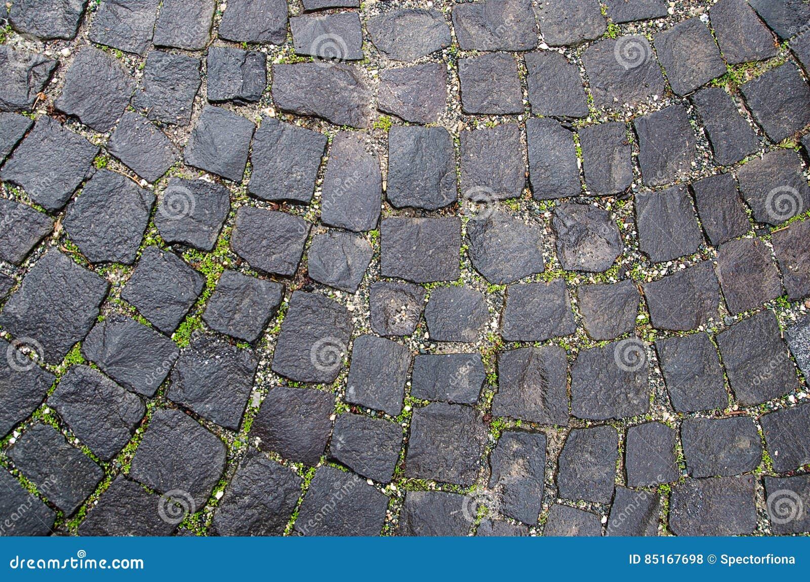 De textuur van de steenbestrating Het graniet cobblestoned achtergrond Samenvatting van oud keiclose-up naadloos praag