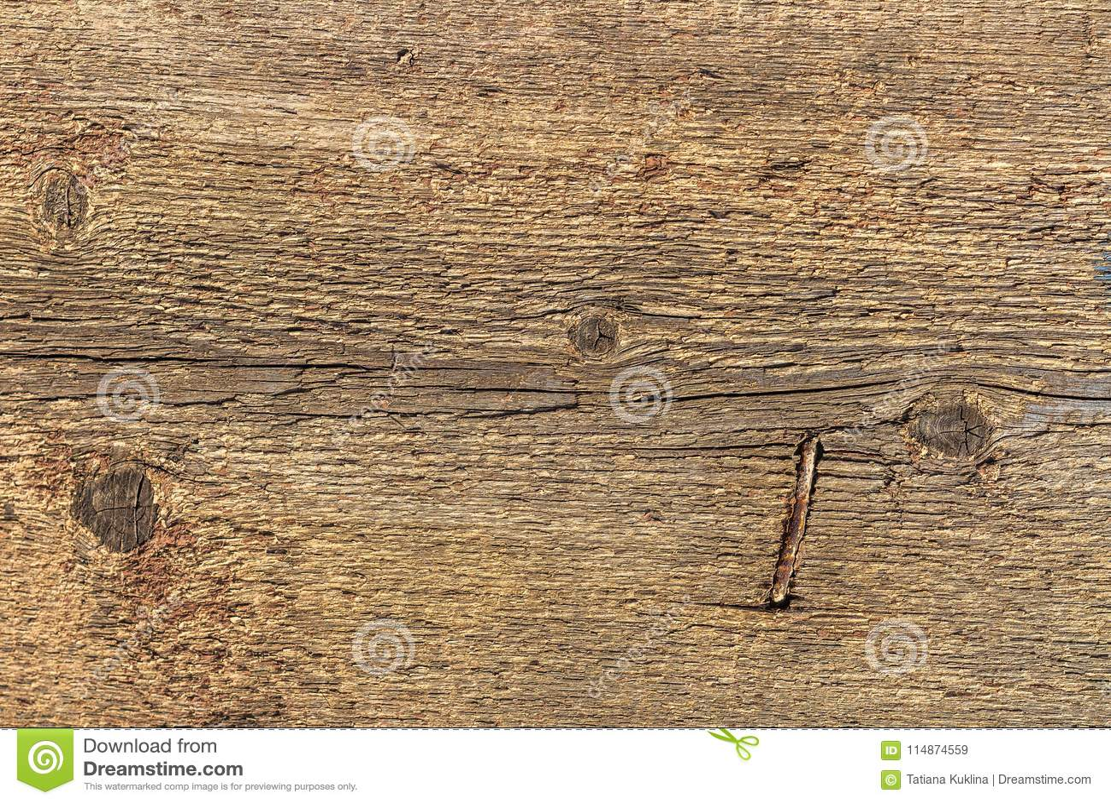 De textuur van oud grijs en geel hout met knopen en roestige gehamerde spijker