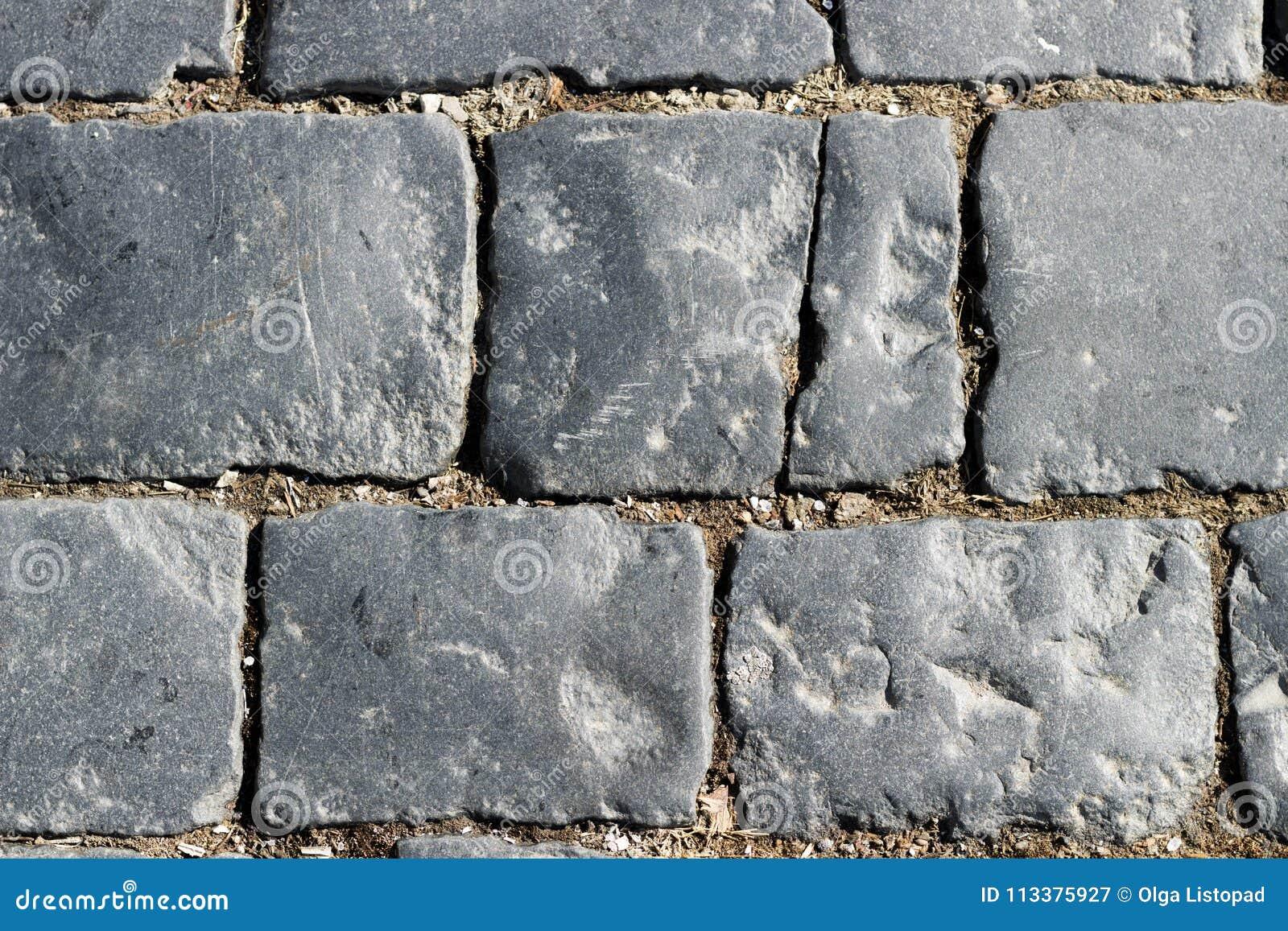 De textuur van de steenbestrating, graniet cobblestoned bestratingsachtergrond, cobbled de regelmatige vormen van de steenweg, ab