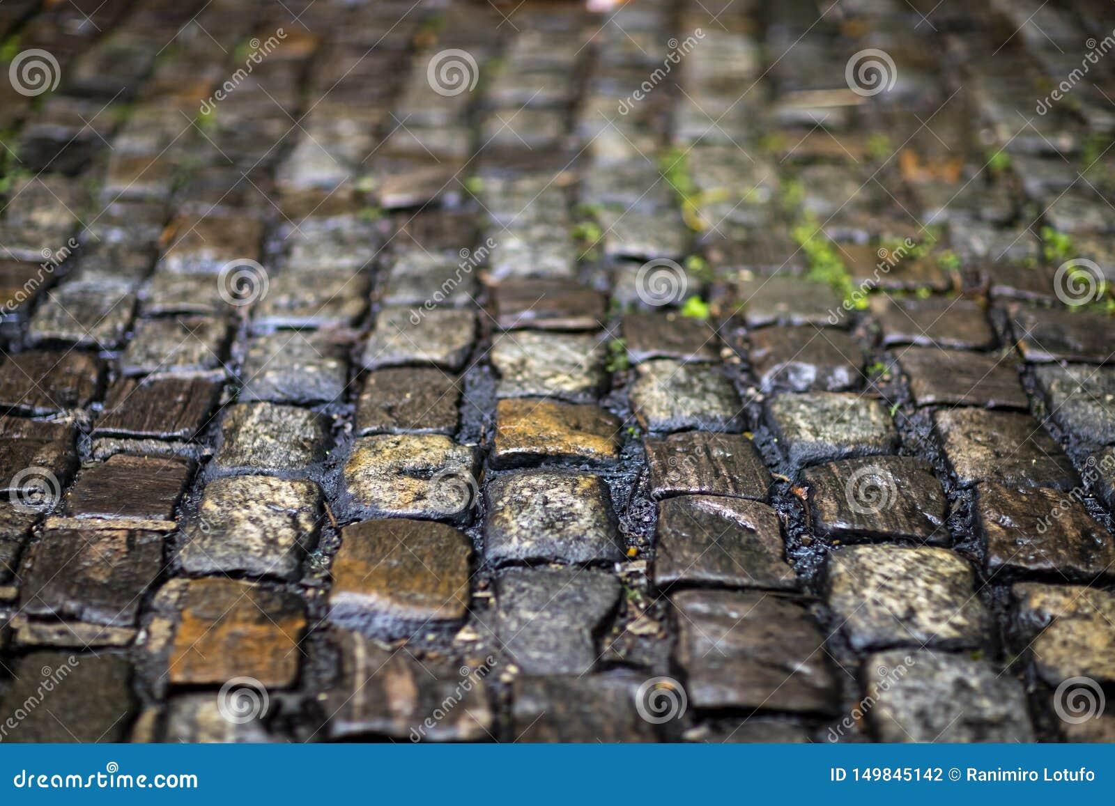 De textuur van de steenbestrating Het graniet cobblestoned bestratingsachtergrond