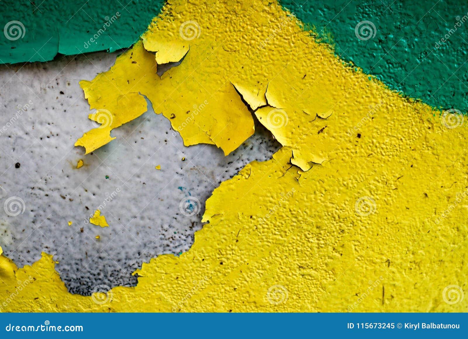 De textuur van twee kleurt gele en groene oude sjofele concrete muur met bolvormige schil varicoloured verf, kuilen en patronen