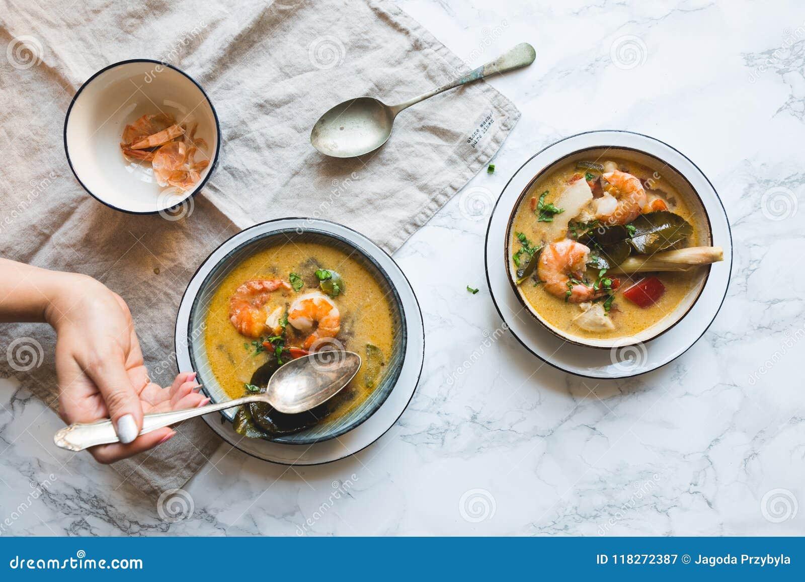 De Thaise Tom Yum Goong-soep met garnalen, garnalen en kaffir bladeren diende op een witte marmeren textuur