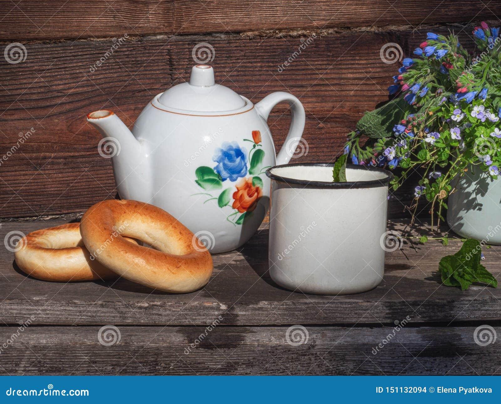 De thee met ongezuurde broodjes en een klein boeket van bloemen in een blauw overvallen op een rustieke portiek