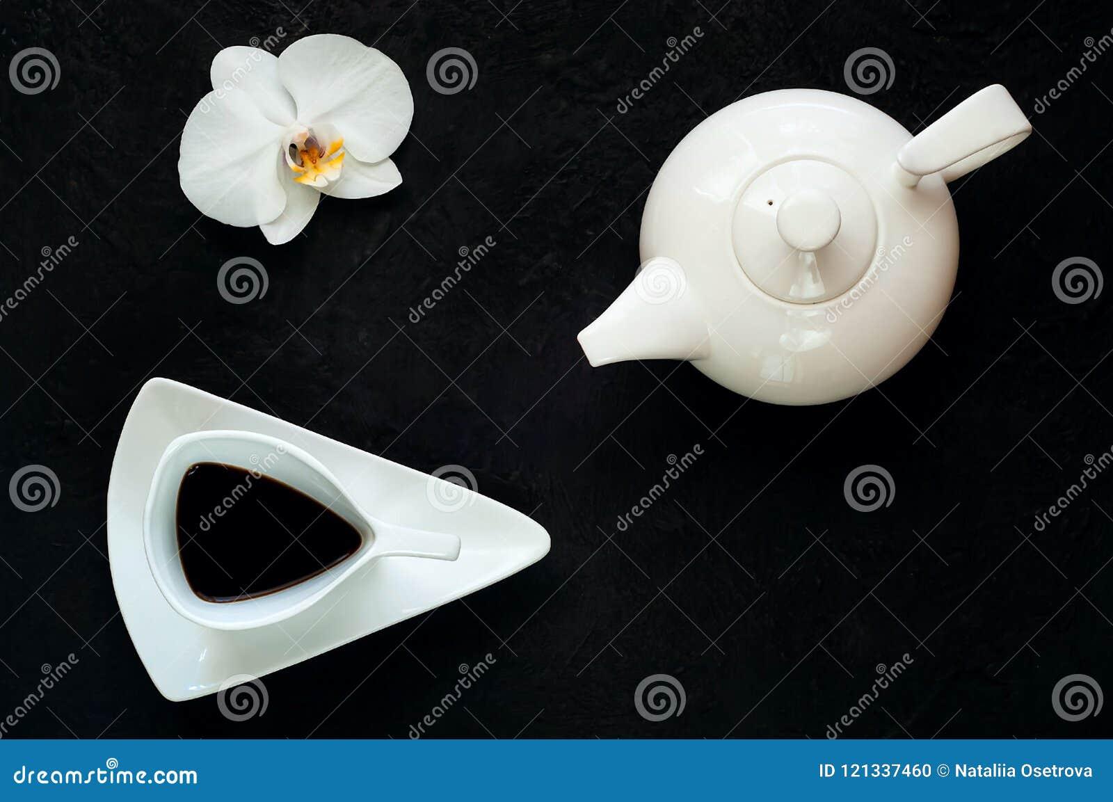 De theepot en de uitstekende witte ceramische kop met thee op donkere achtergrond met orchidee bloeien, kopiëren ruimte, close-up