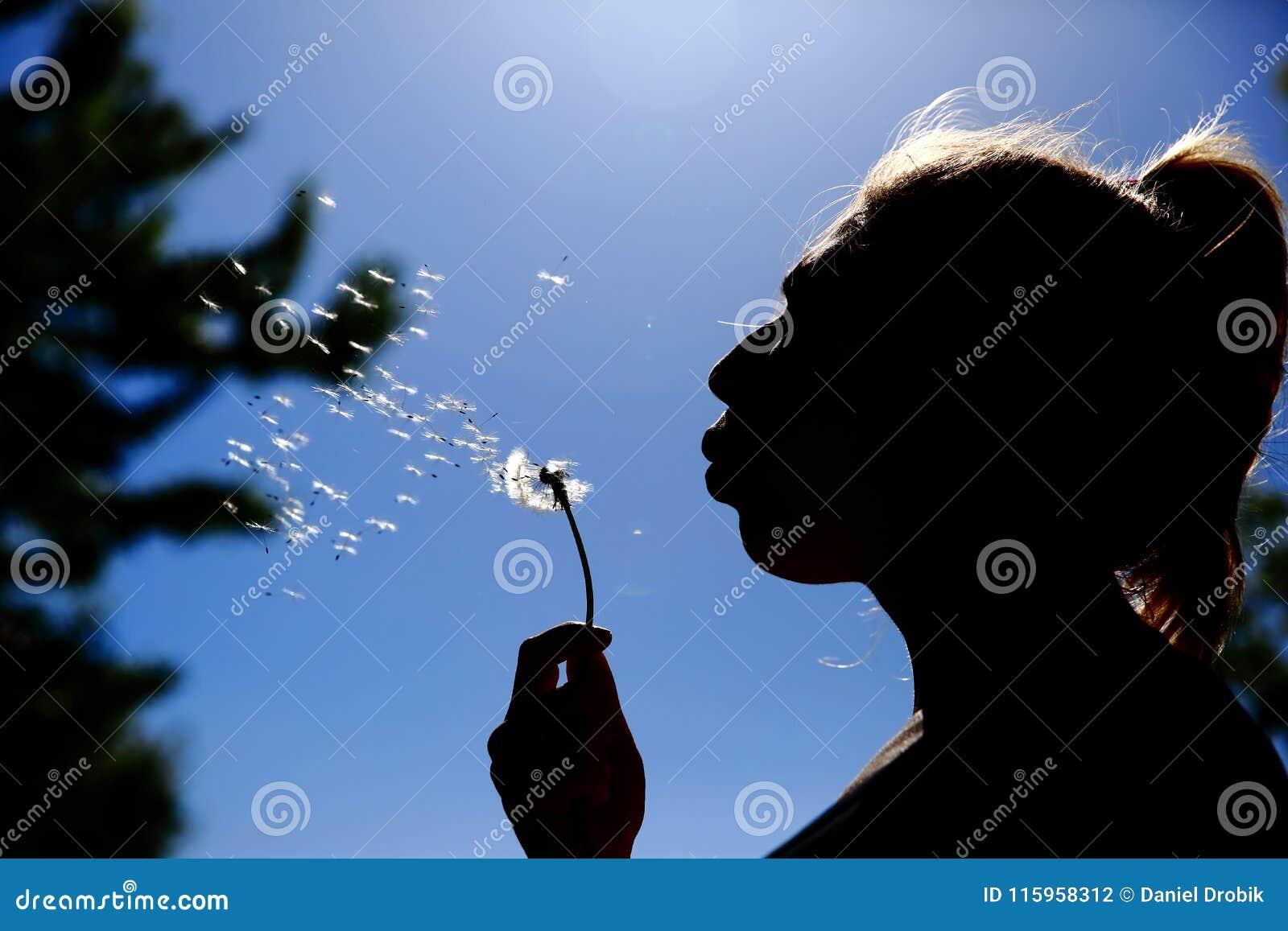 De tiener blaast en spreidt zacht de paardebloemzaden tegen de blauwe hemel uit