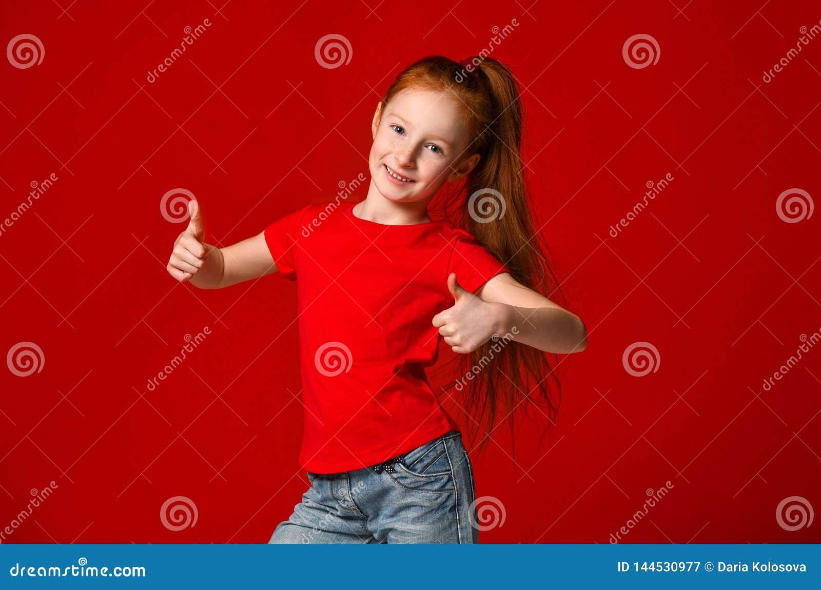 De tiener met gezonde freckled huid, die een rode t-shirt dragen, die de camera bekijken toont grote duimen, gelukkige gelaatsuit