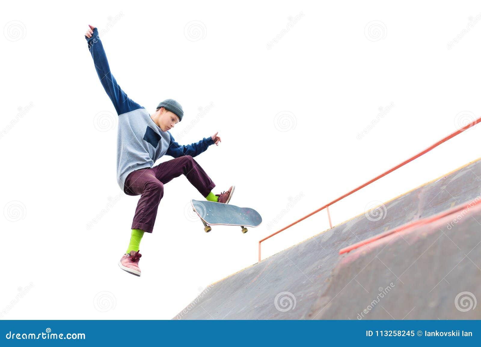 De tiener skateboarder in GLB doet een truc met een sprong op de helling in skatepark Geïsoleerde schaatser en helling