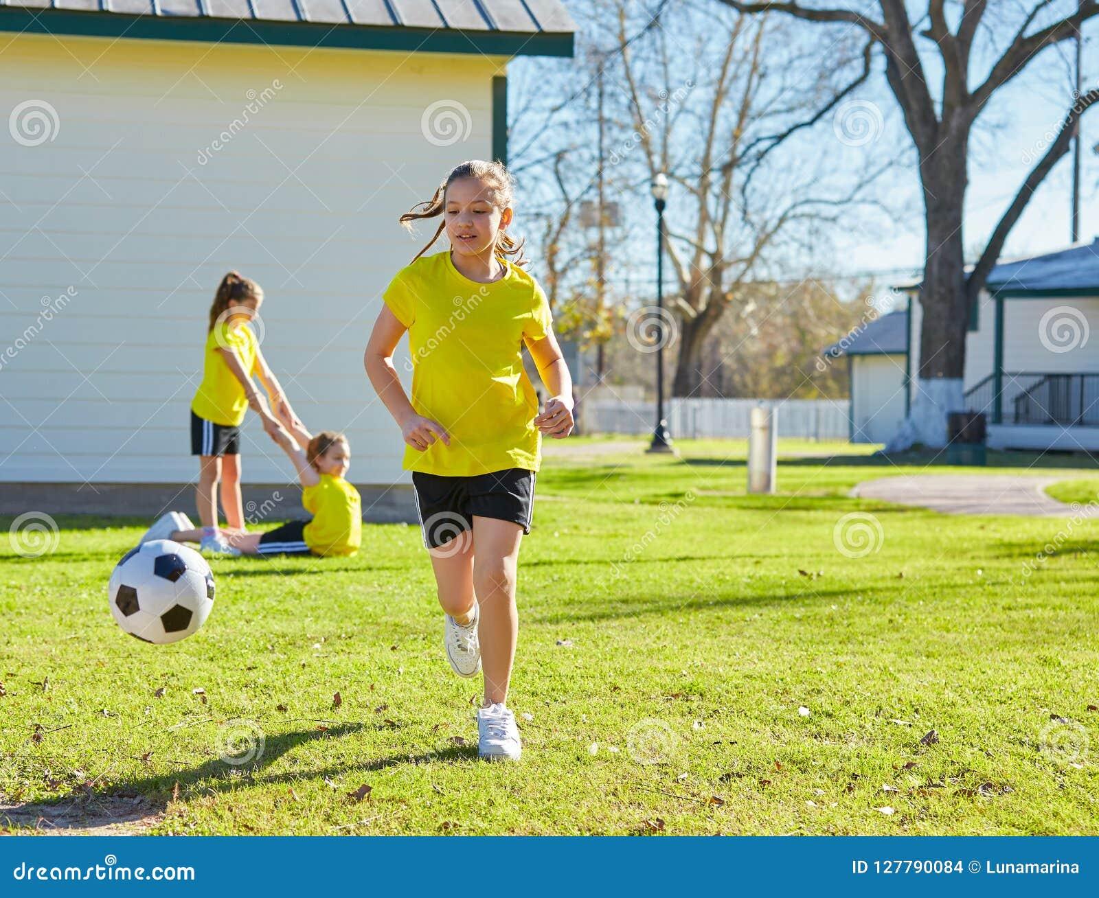 De tienerjaren die van vriendenmeisjes voetbalvoetbal in een park spelen