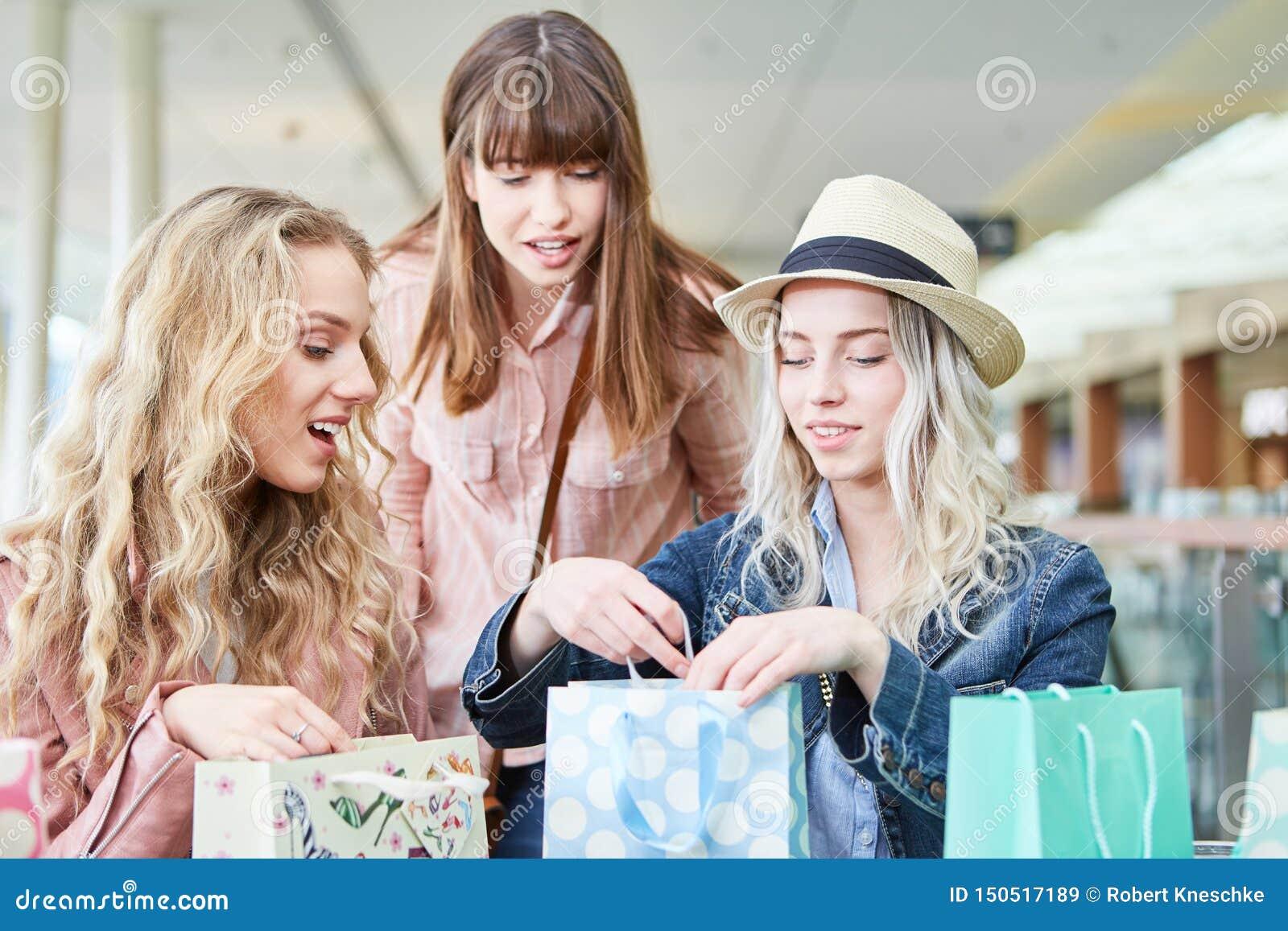De tieners in het winkelen pakken zakken uit