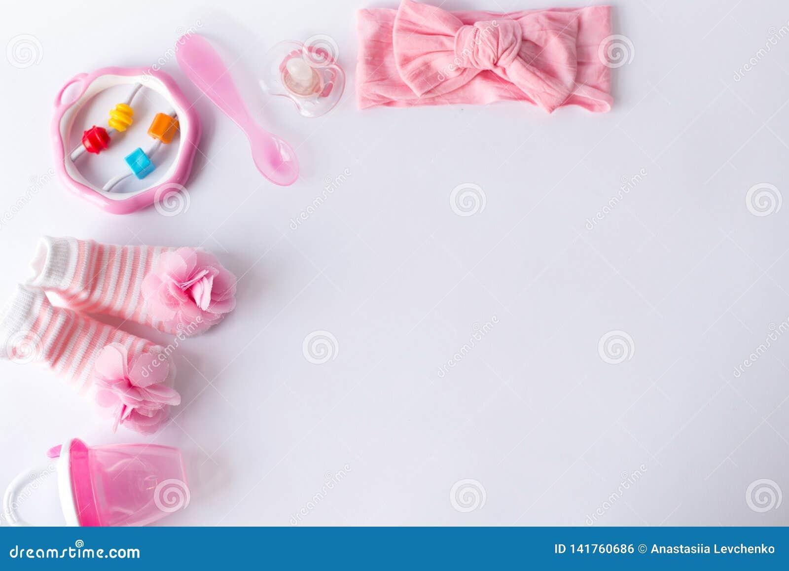 De toebehoren en het speelgoed van het babymeisje op witte achtergrond met lege ruimte voor tekst; de hoogste vlakke mening, legt