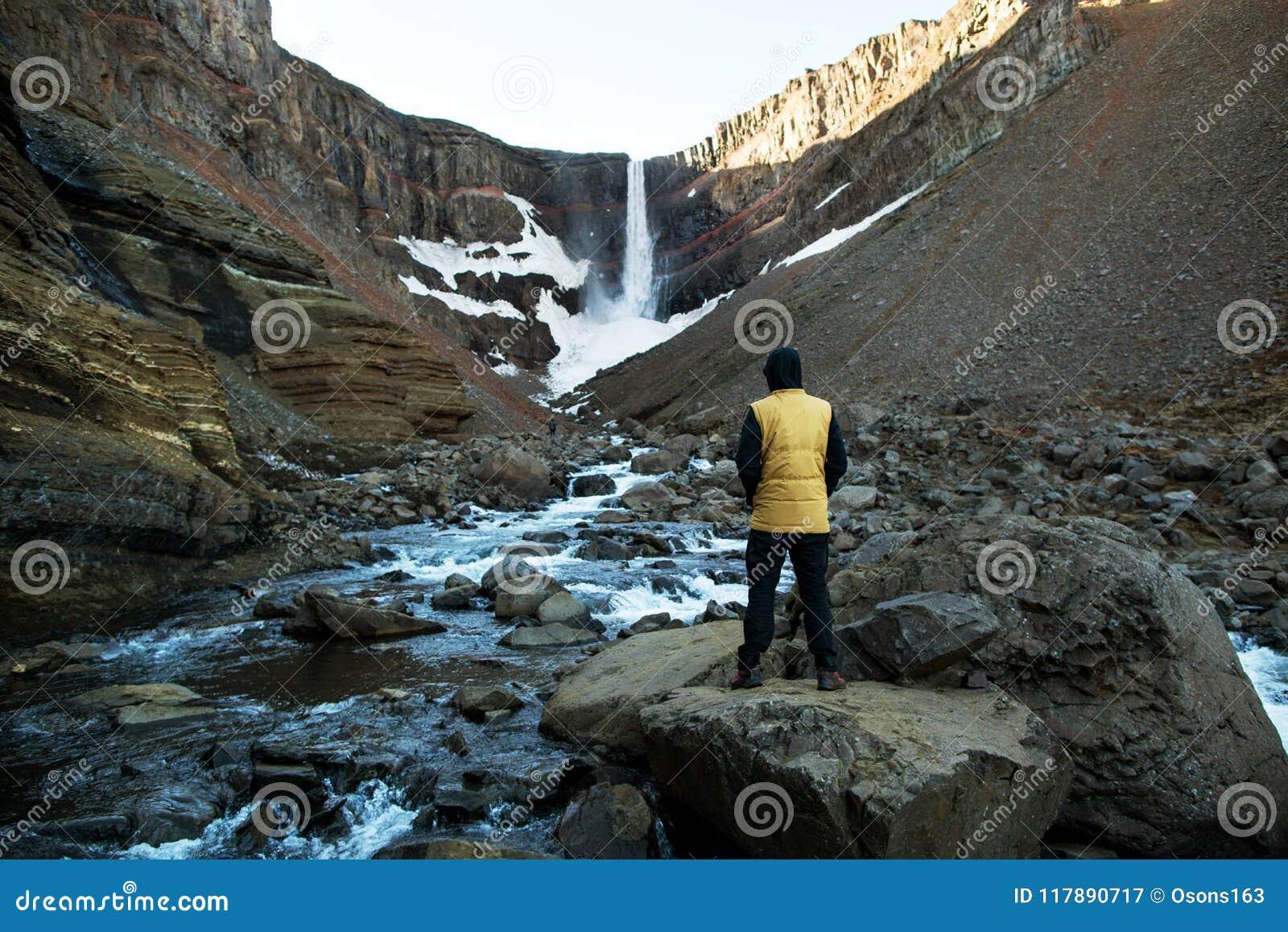 De toerist bevindt zich met zijn rug bekijkend de waterval