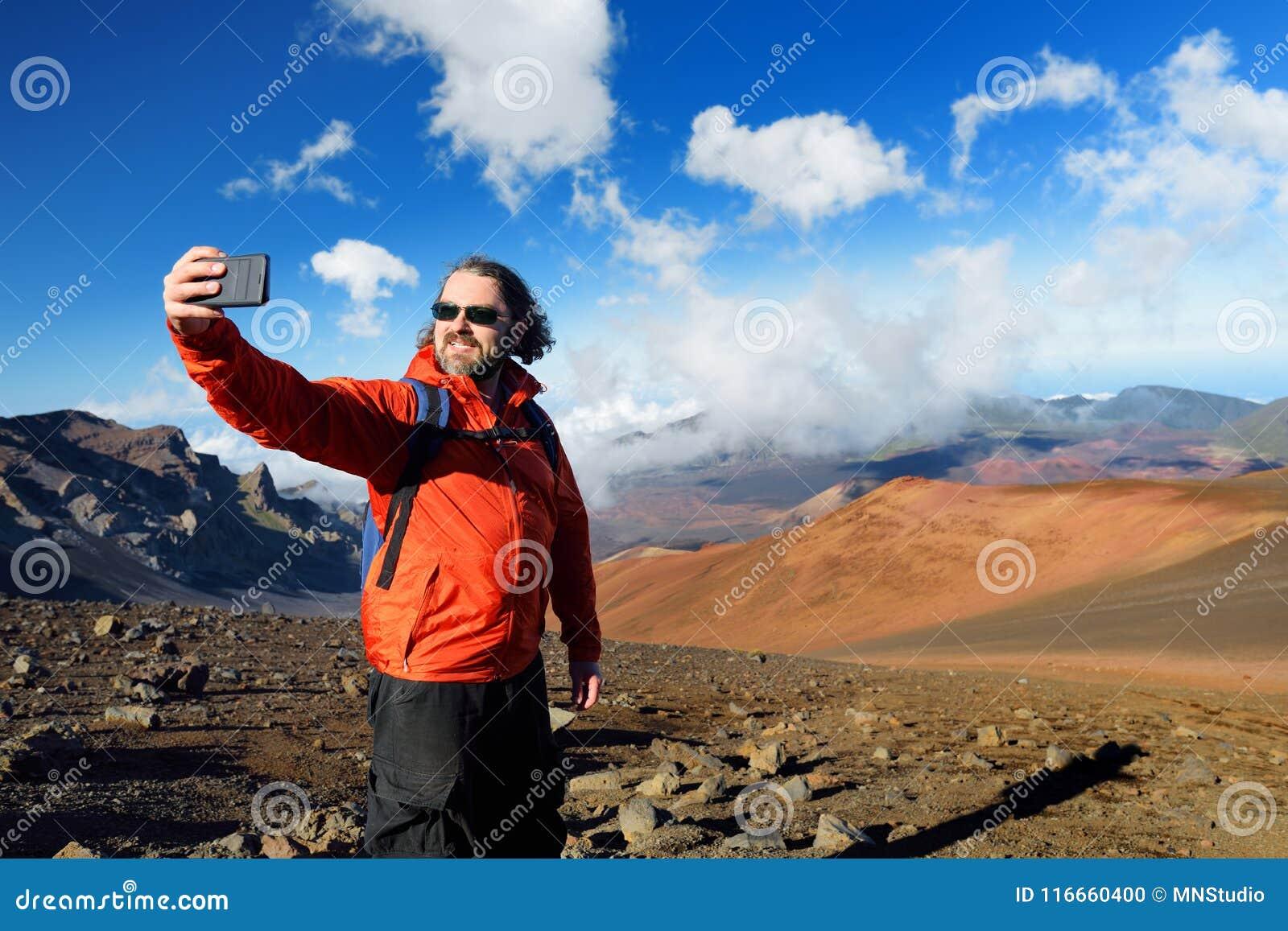 De toerist die een foto van zich in Haleakala-vulkaankrater nemen op het Glijdende Zand sleept Zij worden altijd gevuld met de vo
