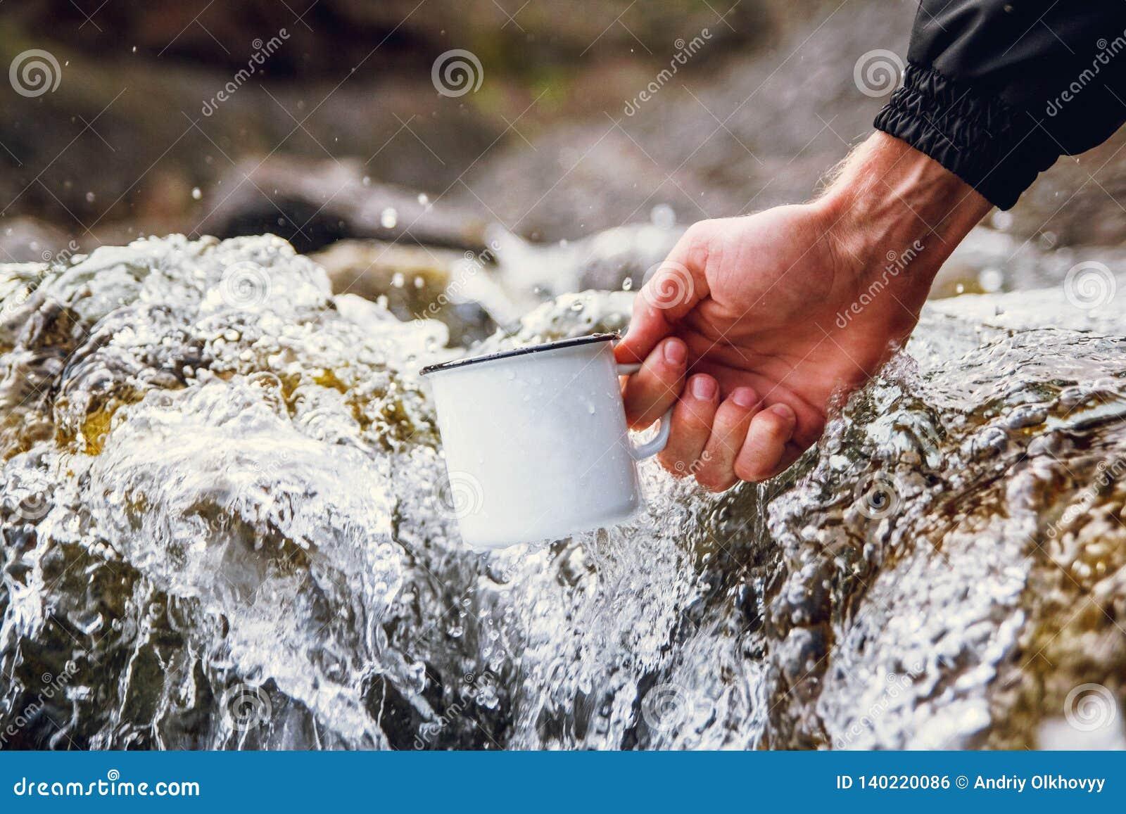 De toerist die van mensen een metaalmok dragen tegen de achtergrond van vage rivieren