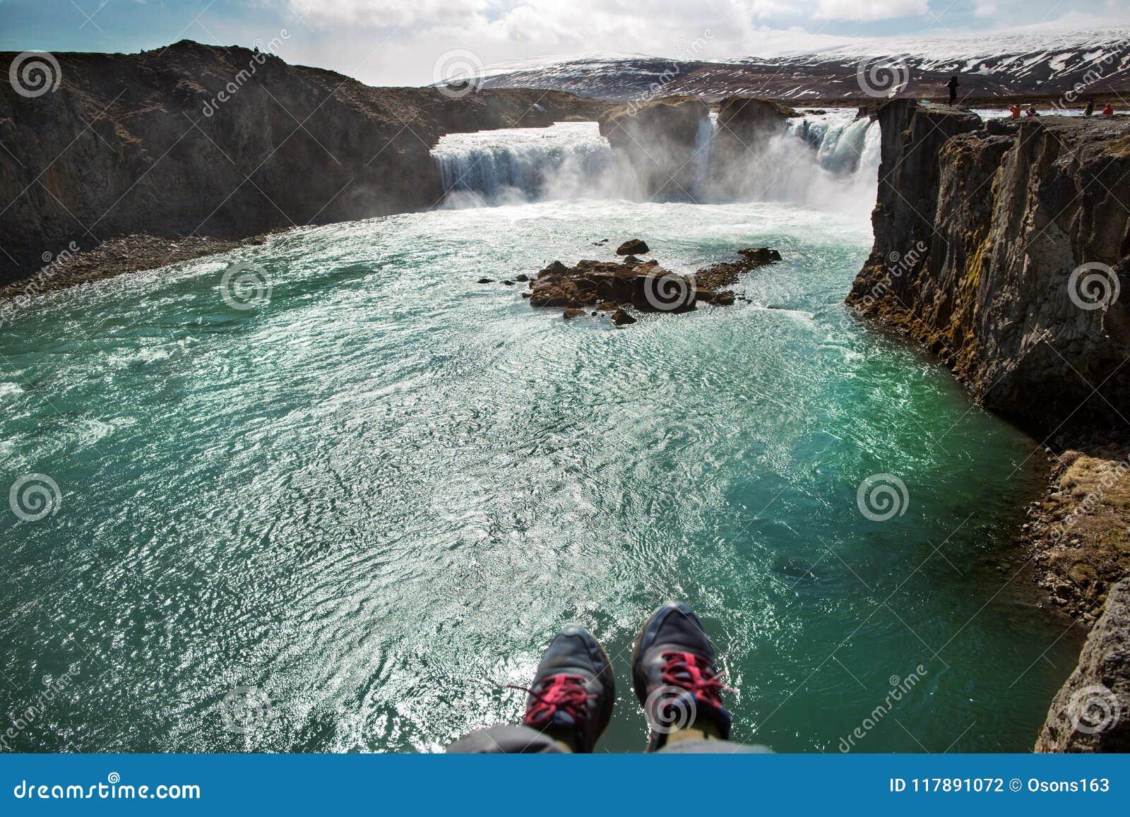 De toerist zit op een klip dichtbij de rivier, die zijn benen hangen neer, v