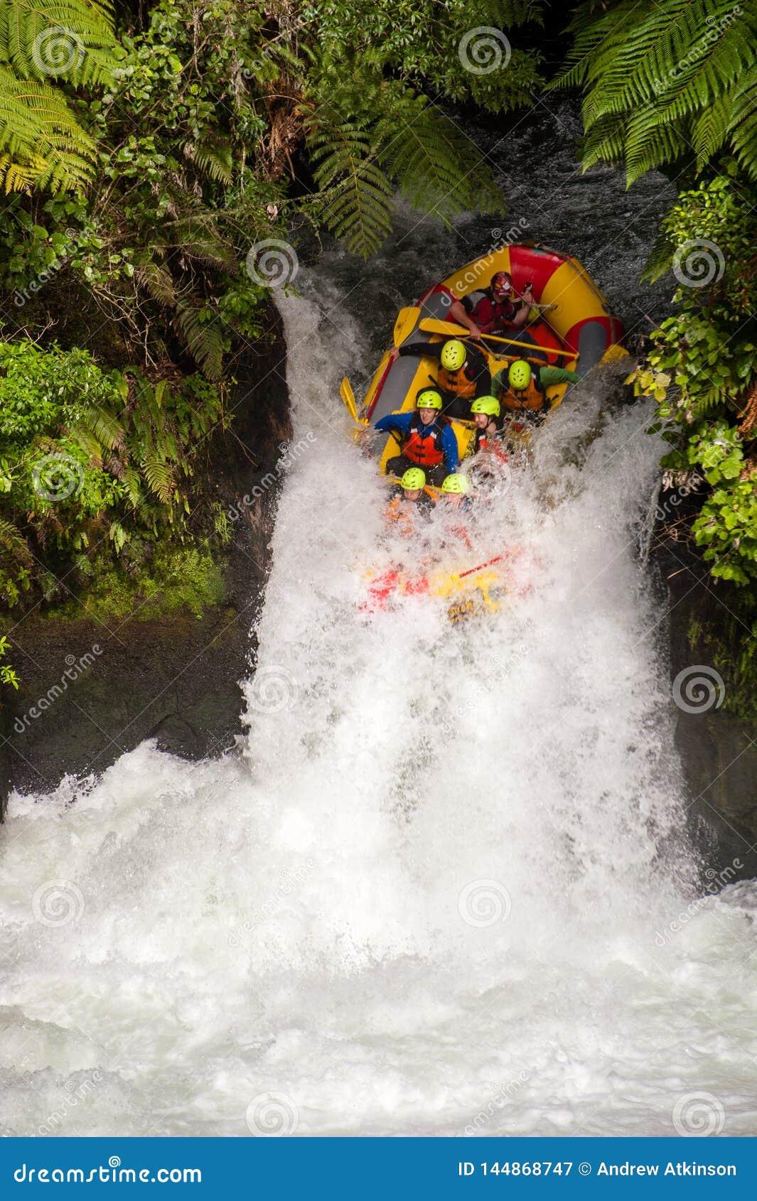 De toeristen werpen zich onderaan een waterval op een stroomversnelling rafting cursus bij Kaituna-Cascades in Rotorua Nieuw Zeel