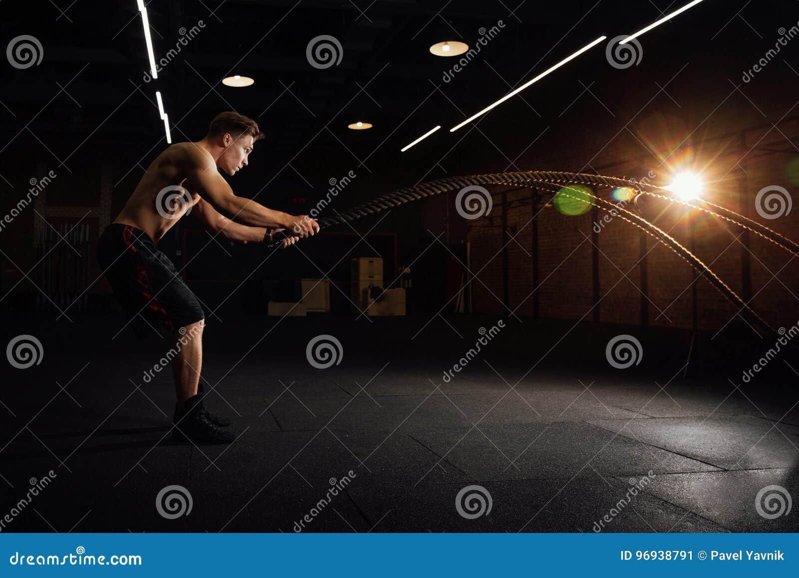 De training van de geschiktheidsmens met slagkabels bij gymnastiek de opleiding van oefening gepast lichaam in club torso