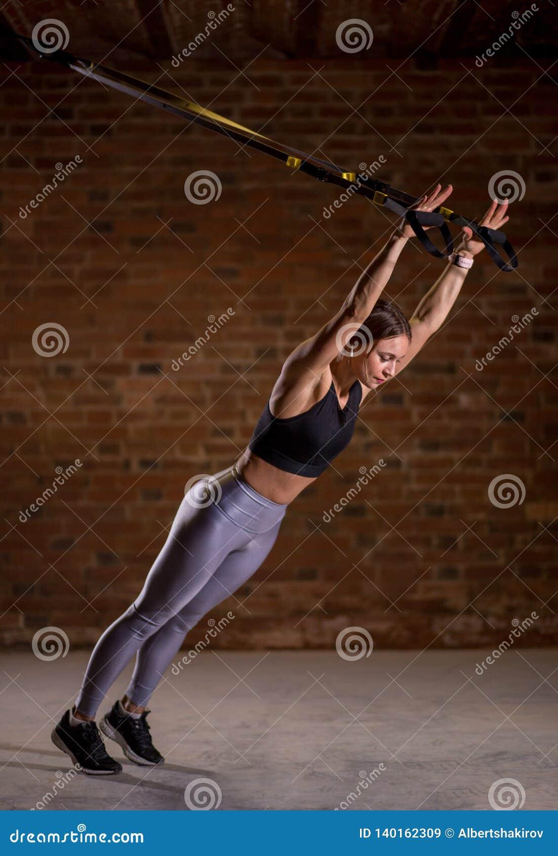 De training van de geschiktheidsvrouw op TRX-riemen in gymnastiek Crossfitstijl Opleiding TRX