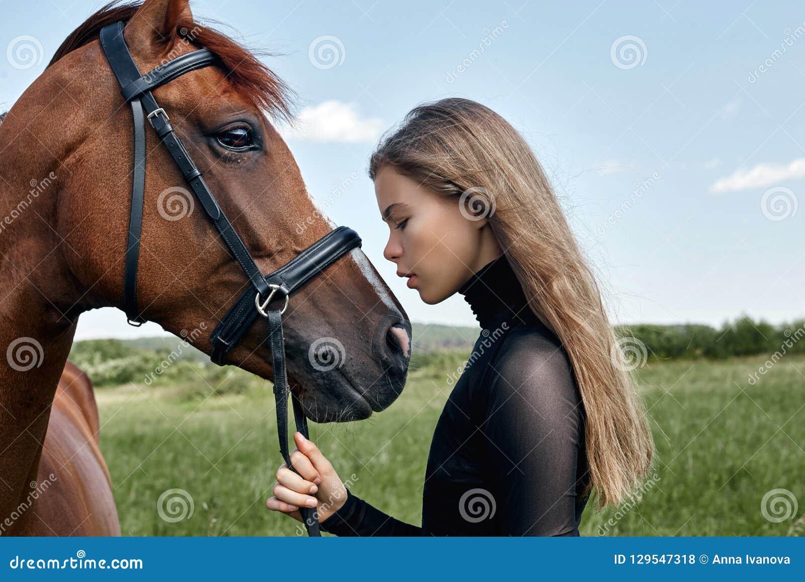 De tribunes van de meisjesruiter naast het paard op het gebied Het manierportret van een vrouw en de merries zijn paarden in het