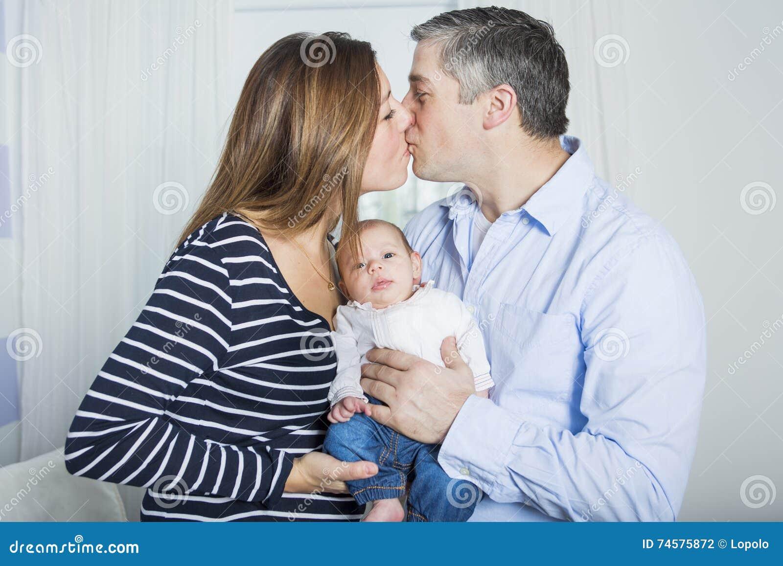 de trotse baby van de oudersholding in de slaapkamer