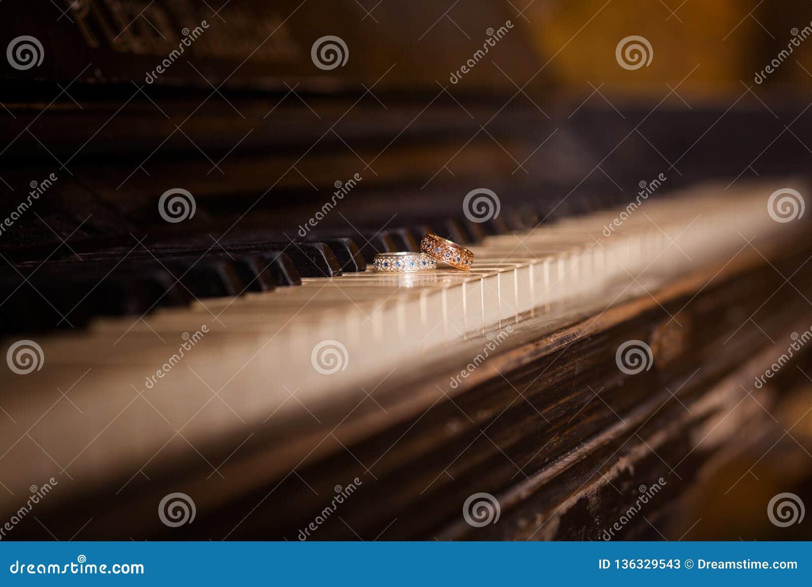 De trouwringen liggen op de pianosleutels