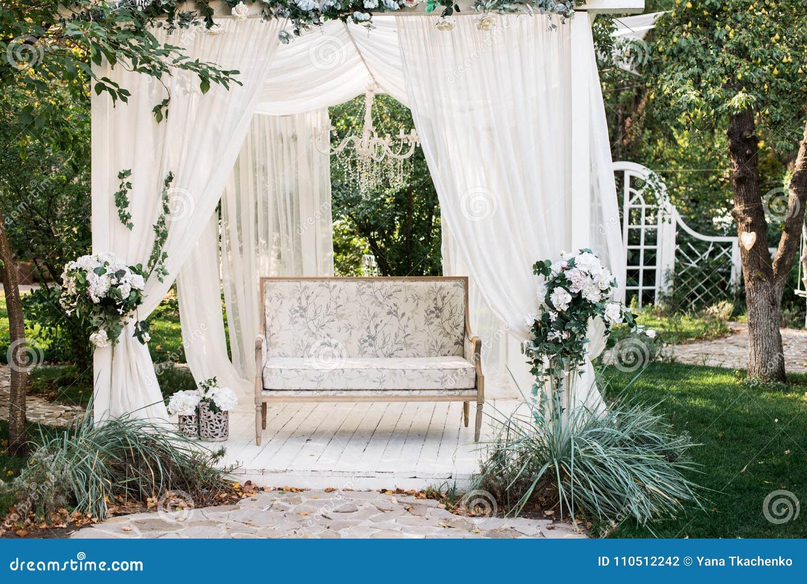 In de tuin is er een podium waarop een mooie witte bank in de stijl van de Provence of plattelander Boven de bank is een boog met