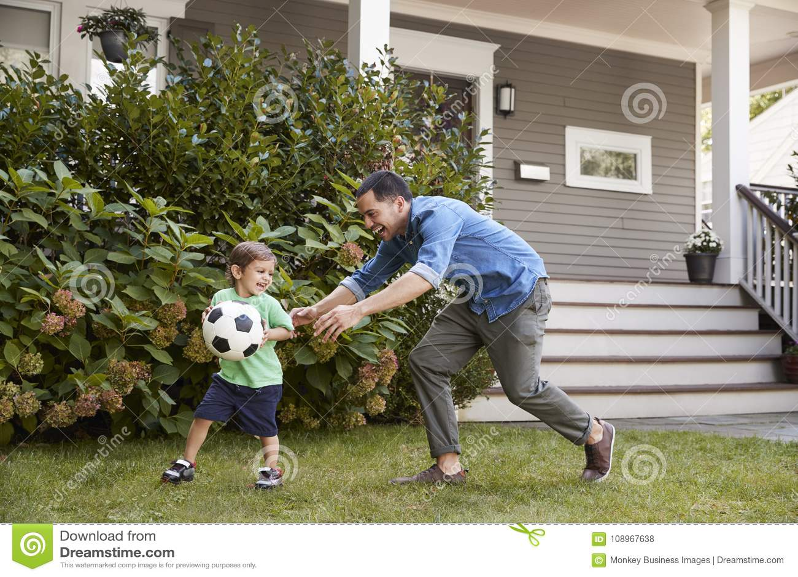 De Tuin van vaderplaying soccer in met Zoon