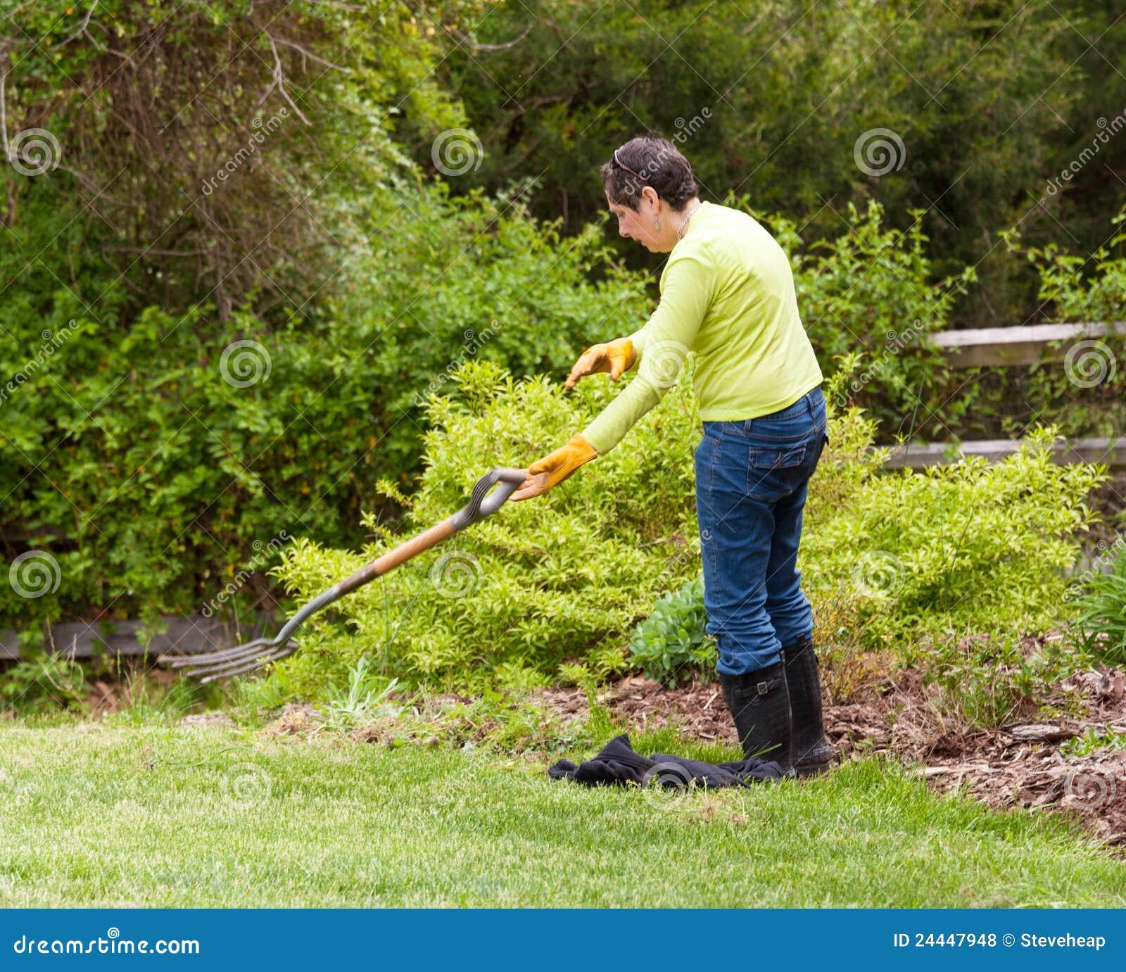 De tuinman van de dame werpt weg vork in frustratie