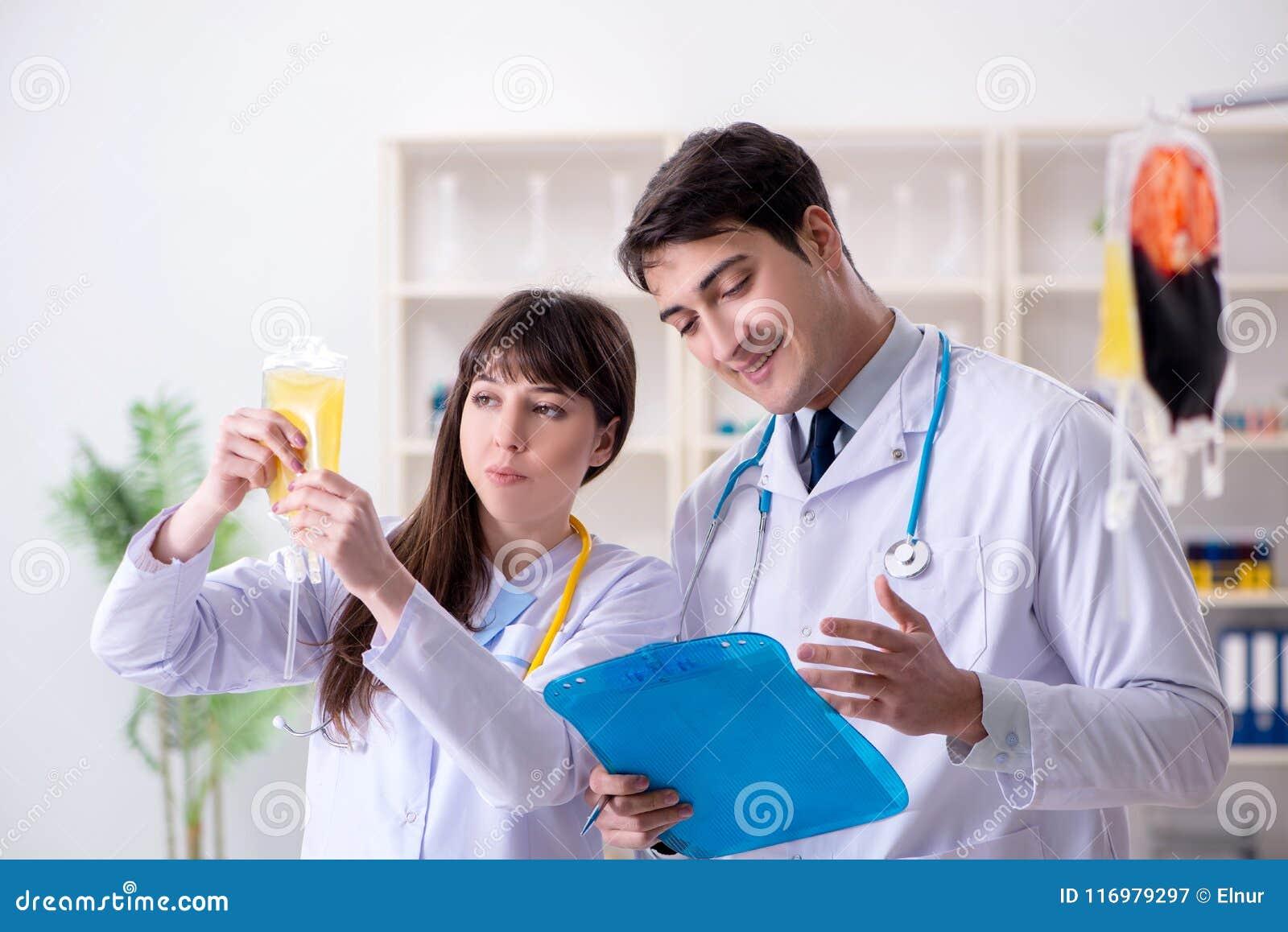 De twee artsen die plasma en bloedtransfusie bespreken
