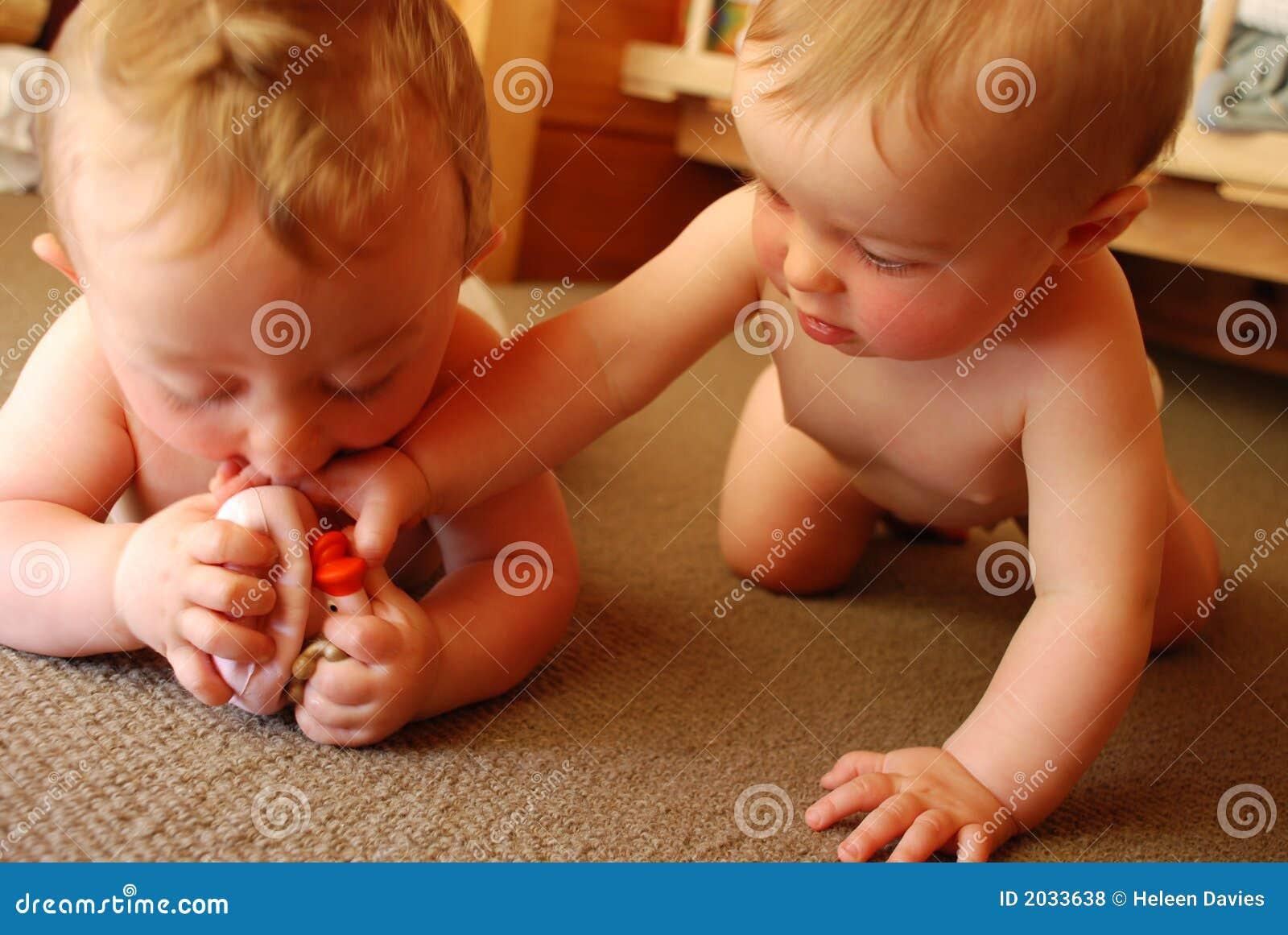 De Tweelingen Die Van De Baby Met Stuk Speelgoed Spelen Royalty-vrije ...