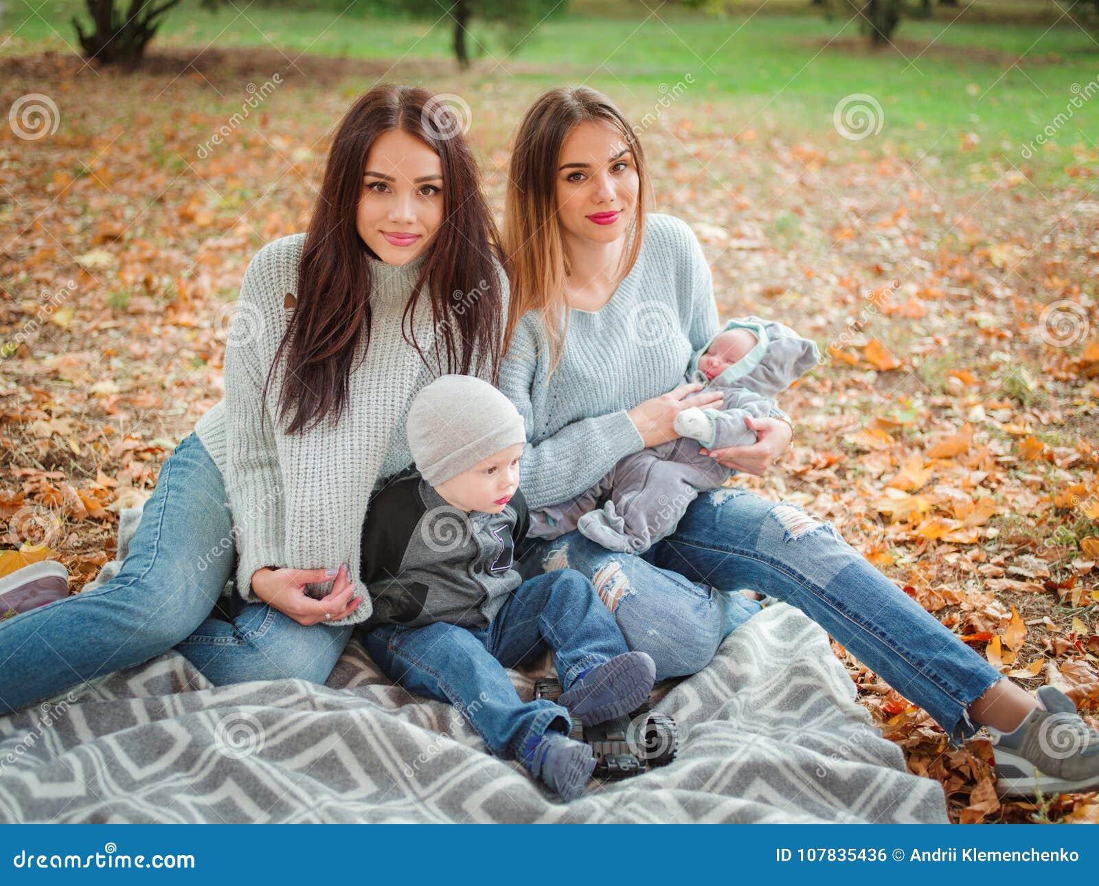 De tweelingmeisjes, zitten in een de herfstpark op een plaid, spelend met een kleine jongen en een baby