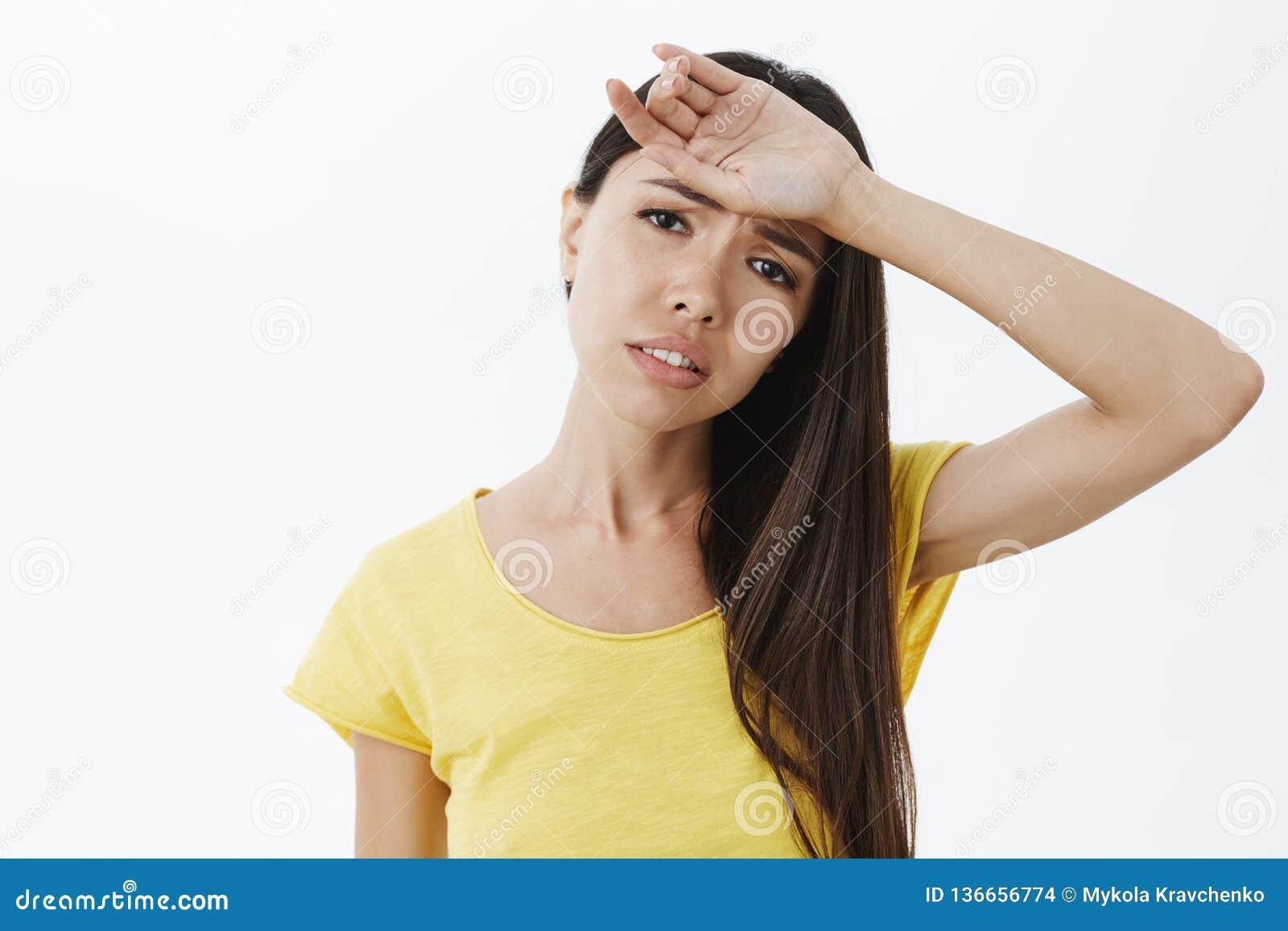 De uitgeputte sombere afgevoerde aantrekkelijke vrouw die met whiping zweet van het lond het mooie donkere haar van voorhoofd put