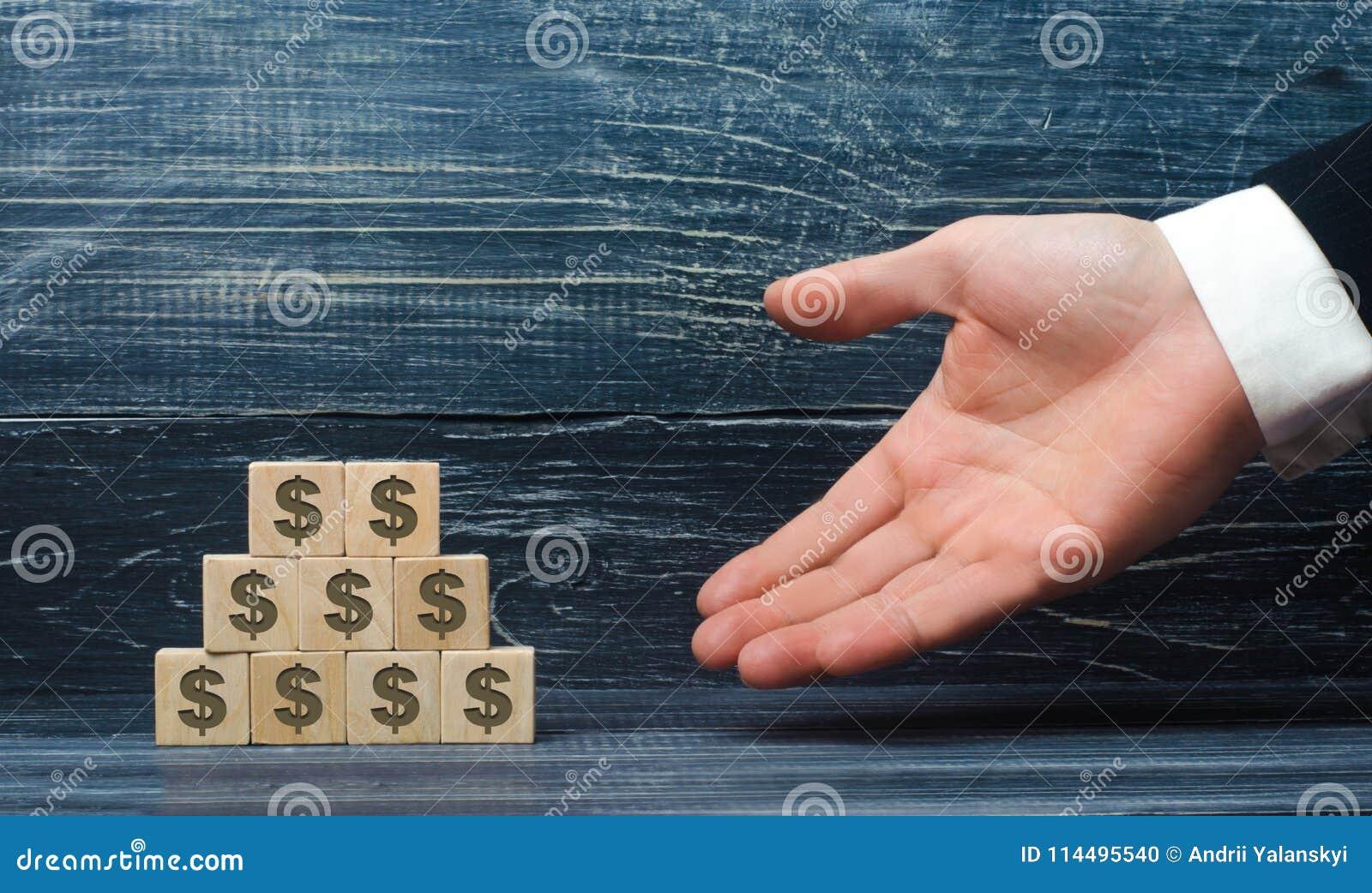 De uitgestrekte hand van een zakenman richt aan een piramide van houten vierkanten met dollarsymbolen Conceptenpromotor, verkoop
