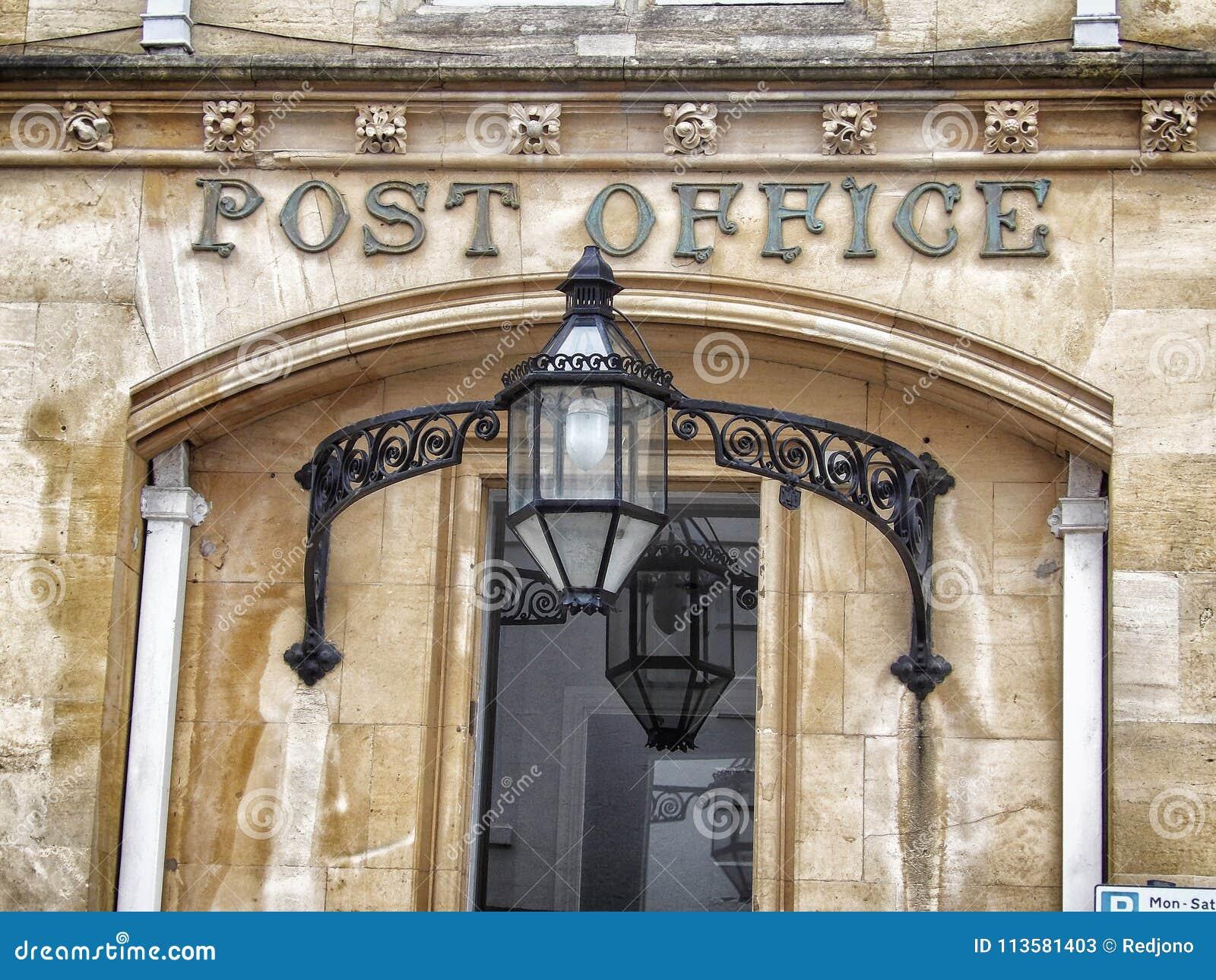 De uitstekende oude postkantoorbouw met teken op ingang