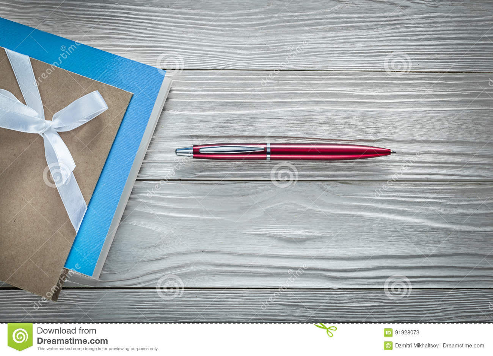 De uitstekende pen van blocnotes rode biro op houten raads horizontaal beeld