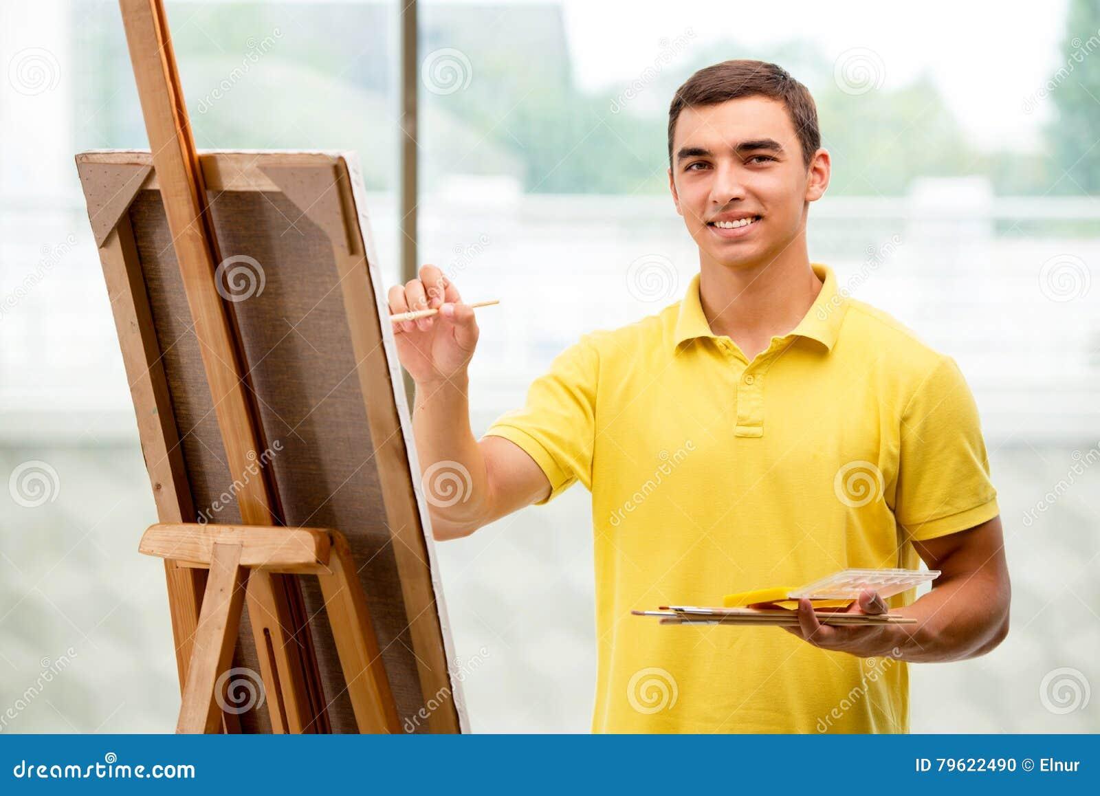 De unga manliga konstnärteckningsbilderna i ljus studio