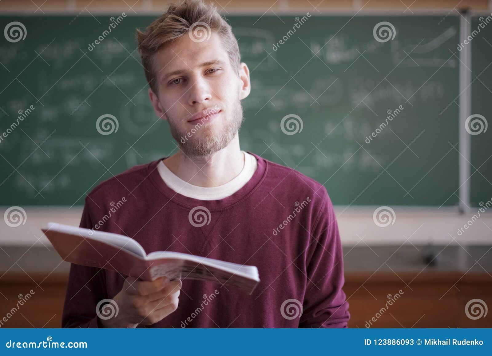 De universitaire jonge mannelijke studenten van het professorsonderwijs in universitair holdingsnotitieboekje met krijt