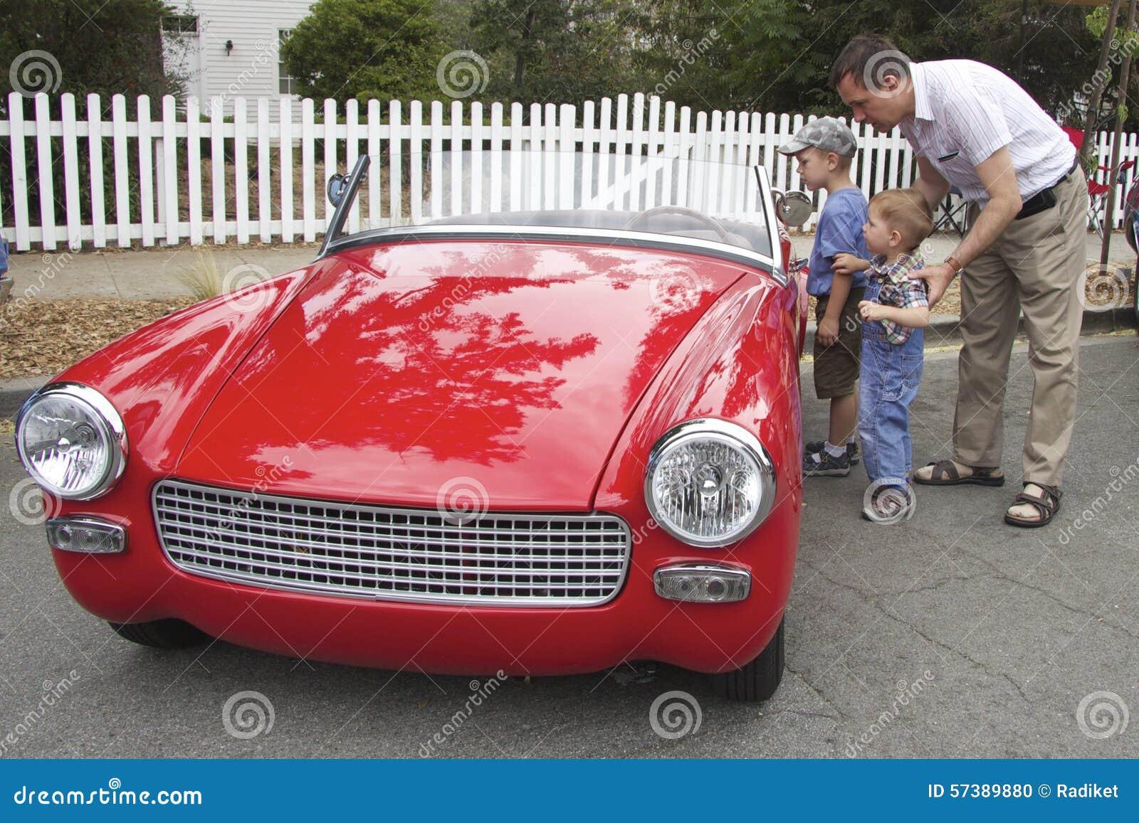De vader en de zonen behandelden kleine rode uitstekende convertibel